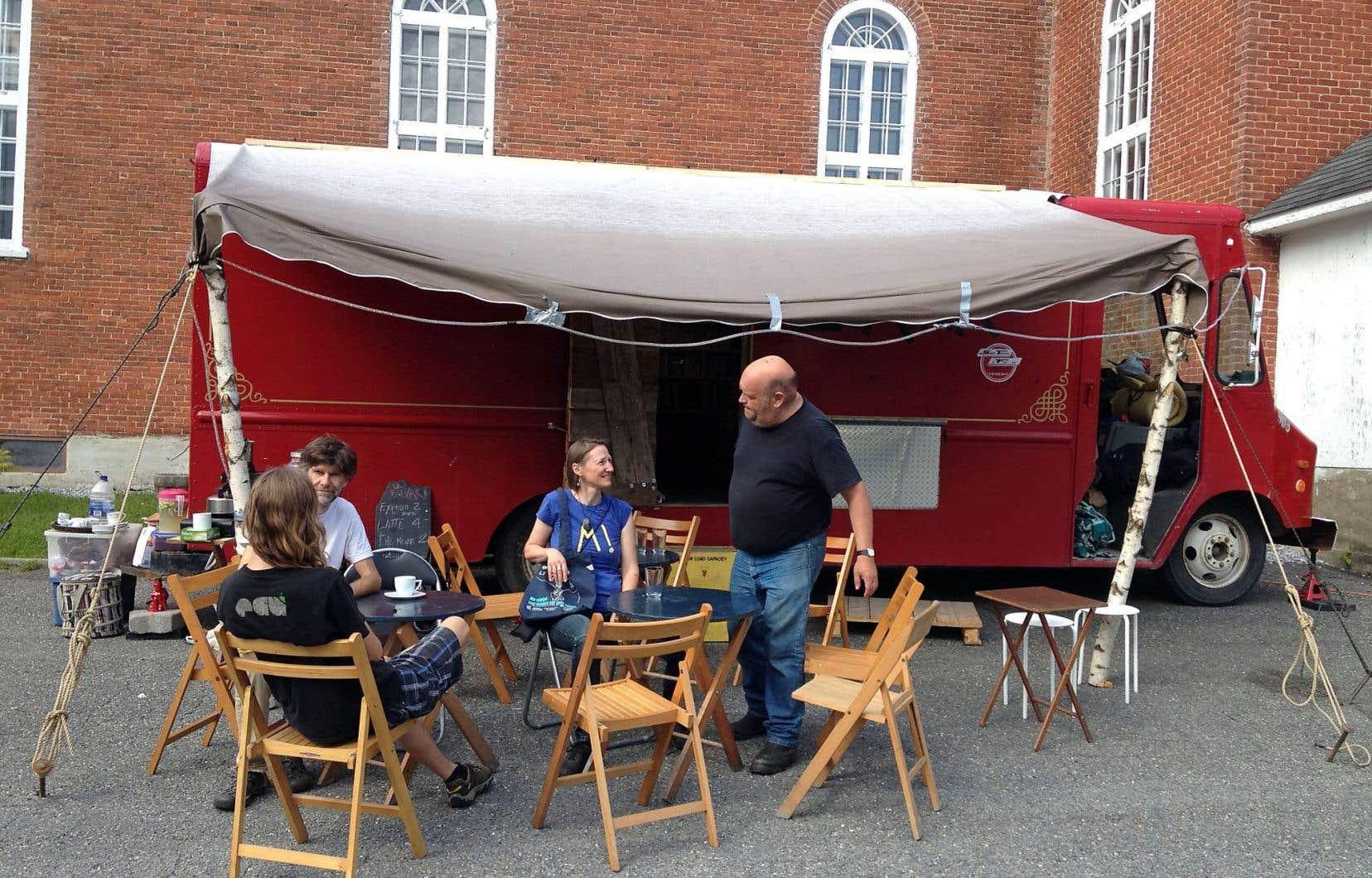 Le libraire Michel Vézina (debout) tient salon littéraire cet été sur les places publiques des villes et villages québécois. Devant son camion-librairie d'allure trash, on prend un café, on cause littérature et on fournit les indications routières aux passants.