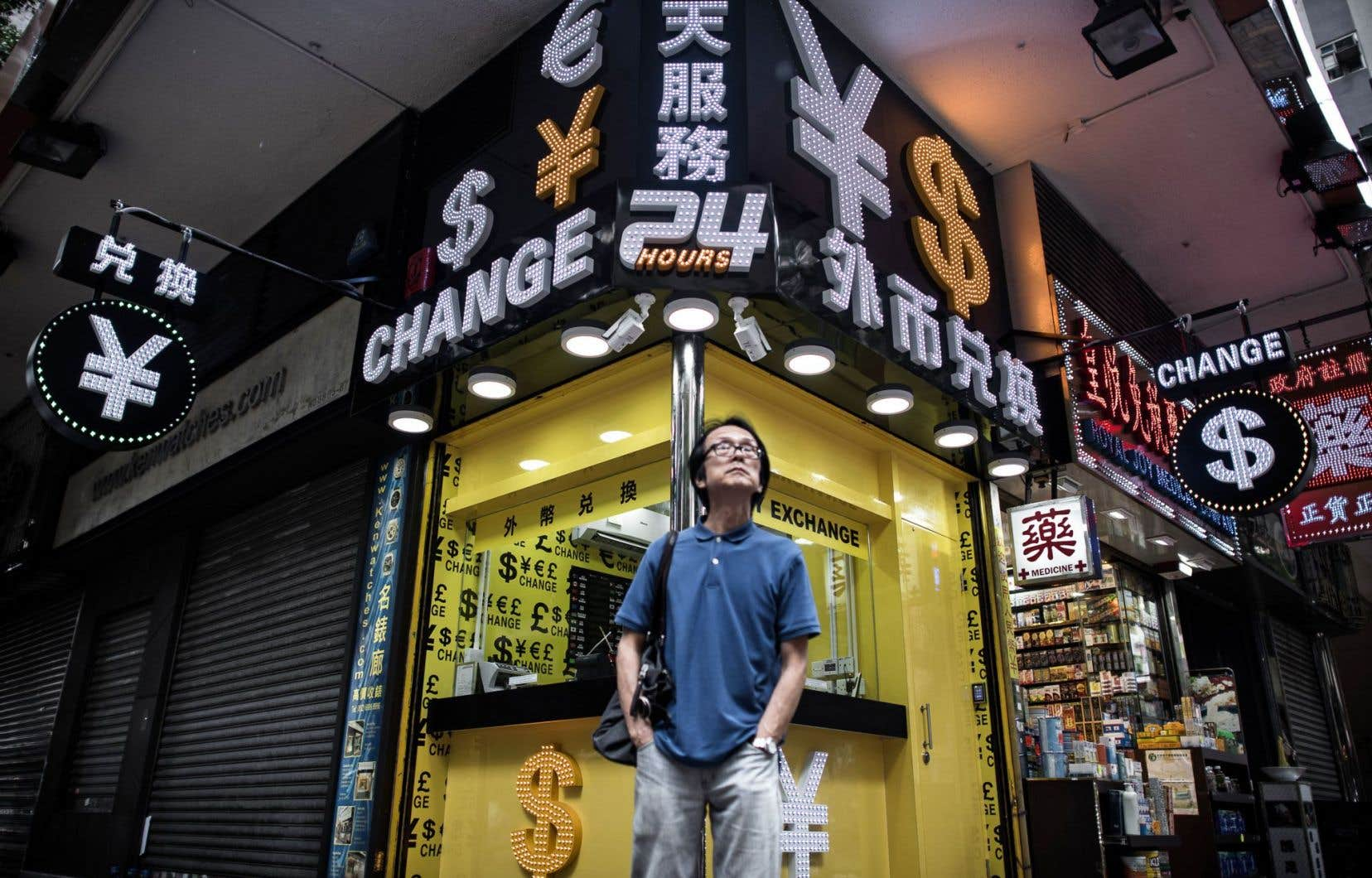 À Hong Kong, un homme se tient debout devant un bureau de change.