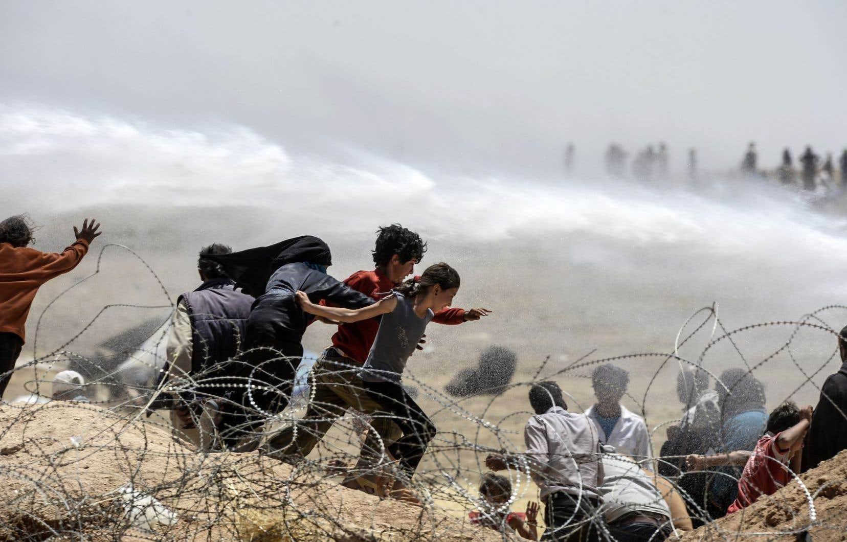 Des réfugiés syriens fuient les jets des canons à eau utilisés par l'armée turque presque quotidiennement pour les éloigner des clôtures de barbelés, à la frontière près de la ville syrienne de Tal Abyad.