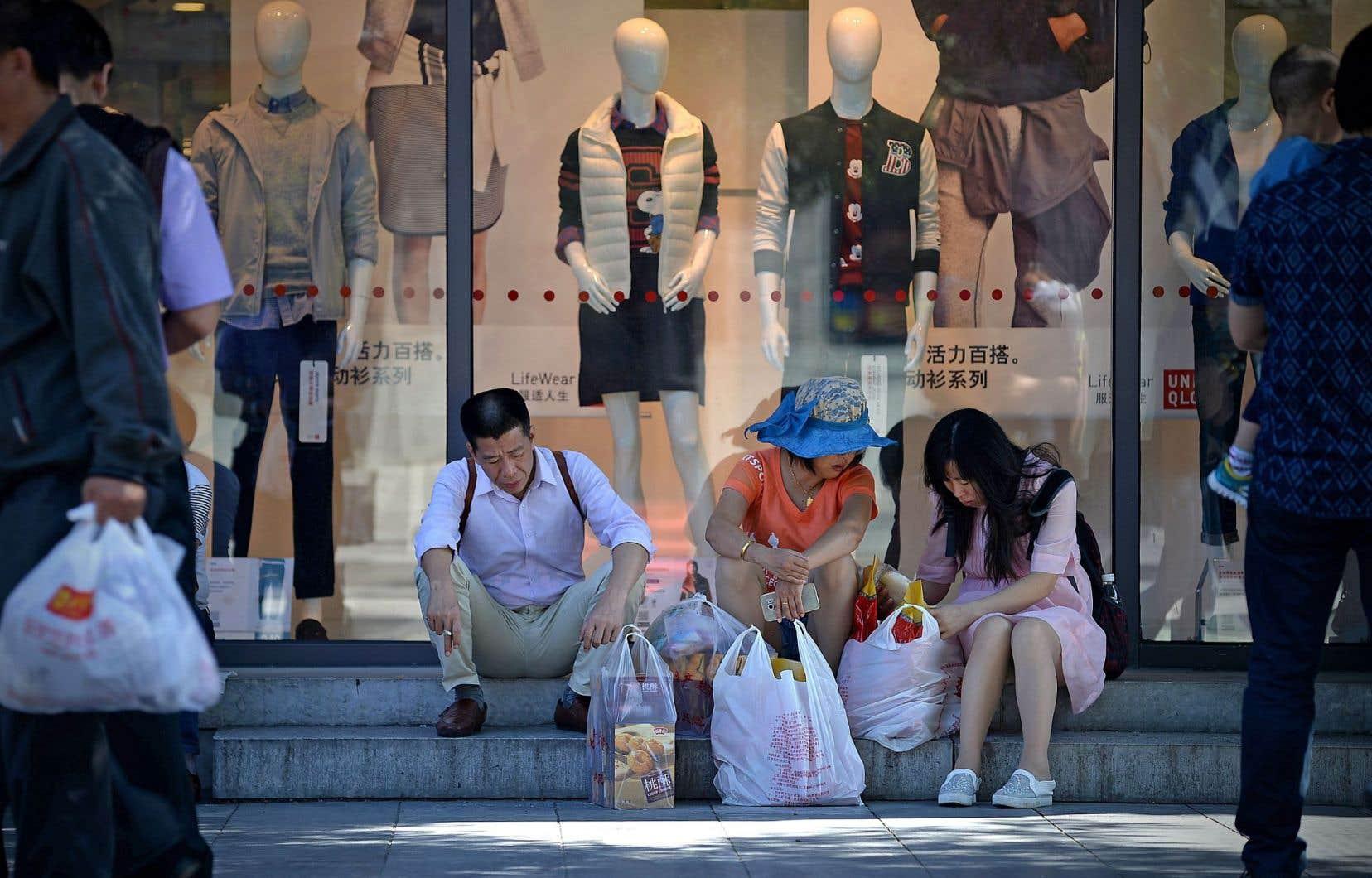 À Pékin, des consommateurs font une pause à l'entrée d'un commerce.