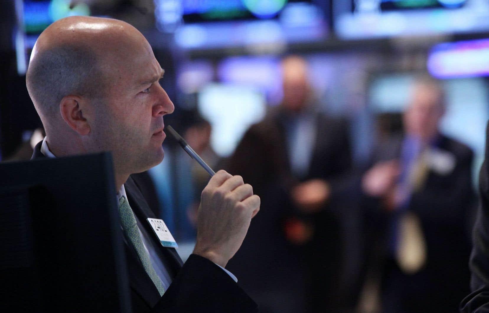 Sur le parquet de la Bourse de New York, un courtier semble s'interroger sur l'interprétation qu'il faut donner aux propos récents de plusieurs responsables de la Banque centrale américaine.