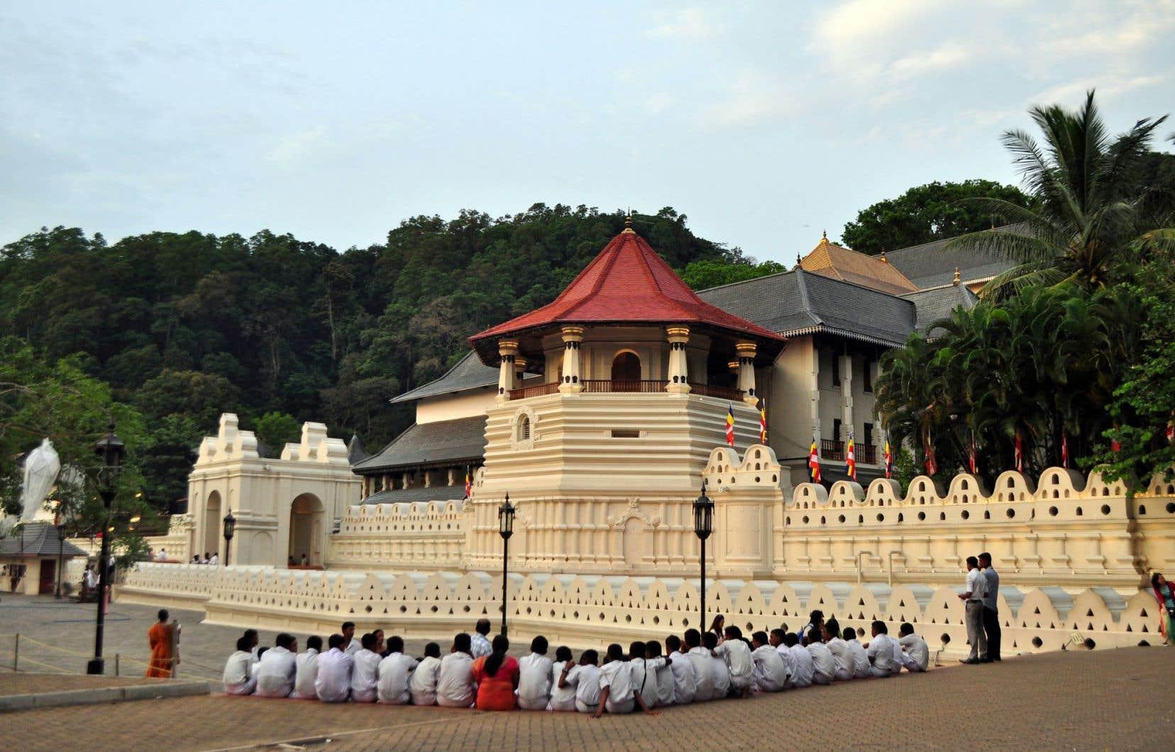 Alors que retentit la prière, au crépuscule, des élèves ont pris place devant le temple de la Dent, à Kandy, haut lieu du bouddhisme au Sri Lanka.