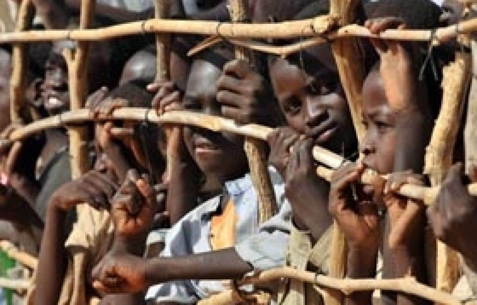 Des enfants pressés contre la clôture délimitant le camp de réfugiés de Goz Beida, hier. La force européenne déployée pendant un an au Tchad et en Centrafrique a passé le flambeau hier à l'ONU, qui s'occupera dorénavant de la sécurité da
