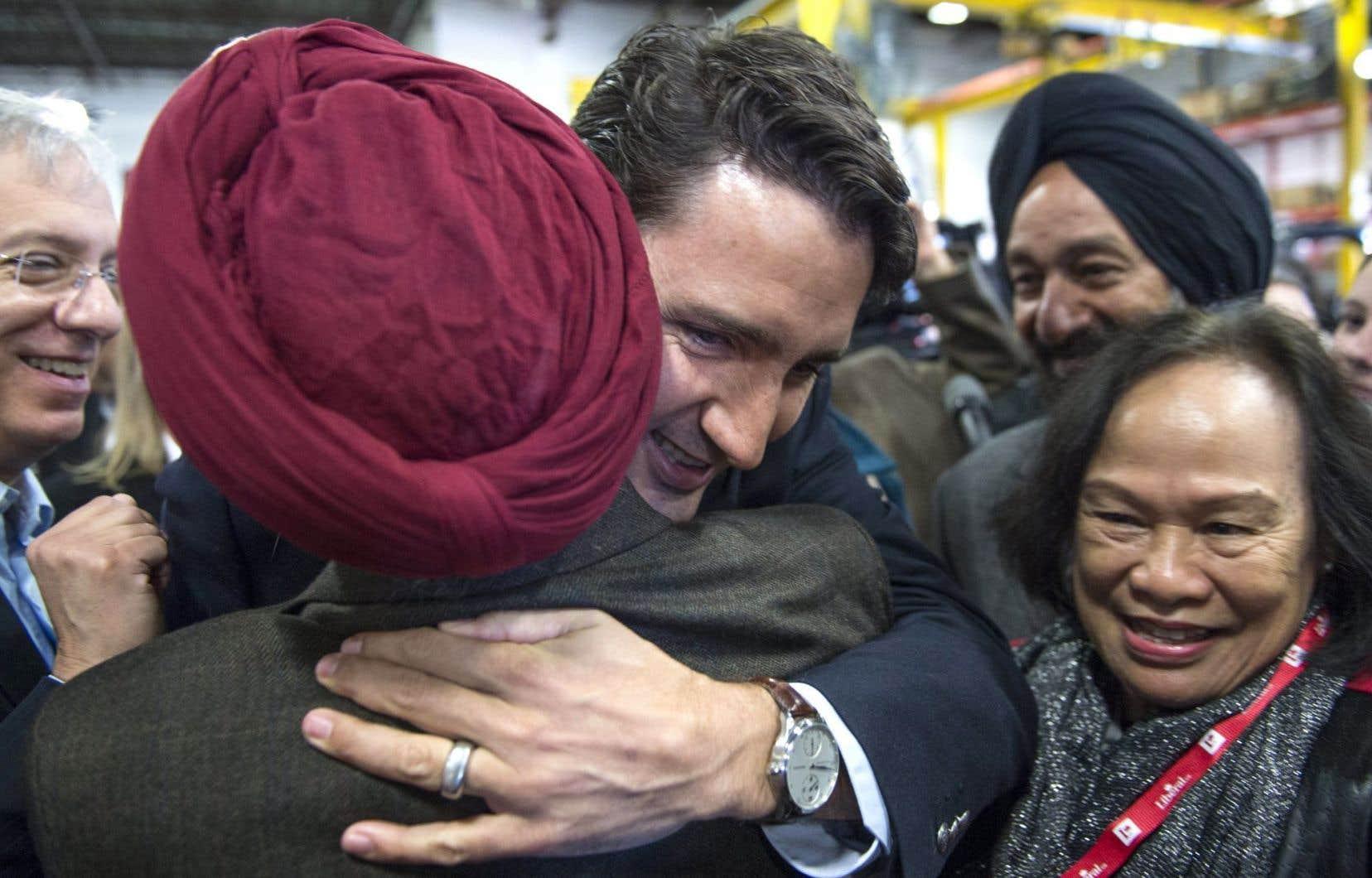 Justin Trudeau reçoit l'accolade d'un militant libéral à Montréal. Le Parti libéral domine maintenant dans les intentions de vote des Canadiens.