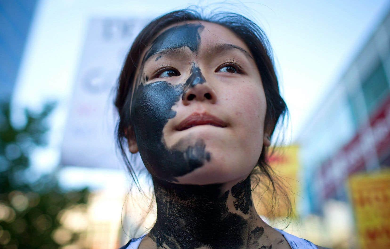 Jacqueline Lee-Tam, le visage maquillé pour évoquer le pétrole des sables bitumineux, au cours d'une manifestation contre le projet de pipeline Northern Gateway. Un rapport du groupe Oil Change International souligne que «tous les projets importants ont été retardés de façon significative, certains au point même d'être annulés sous peu».