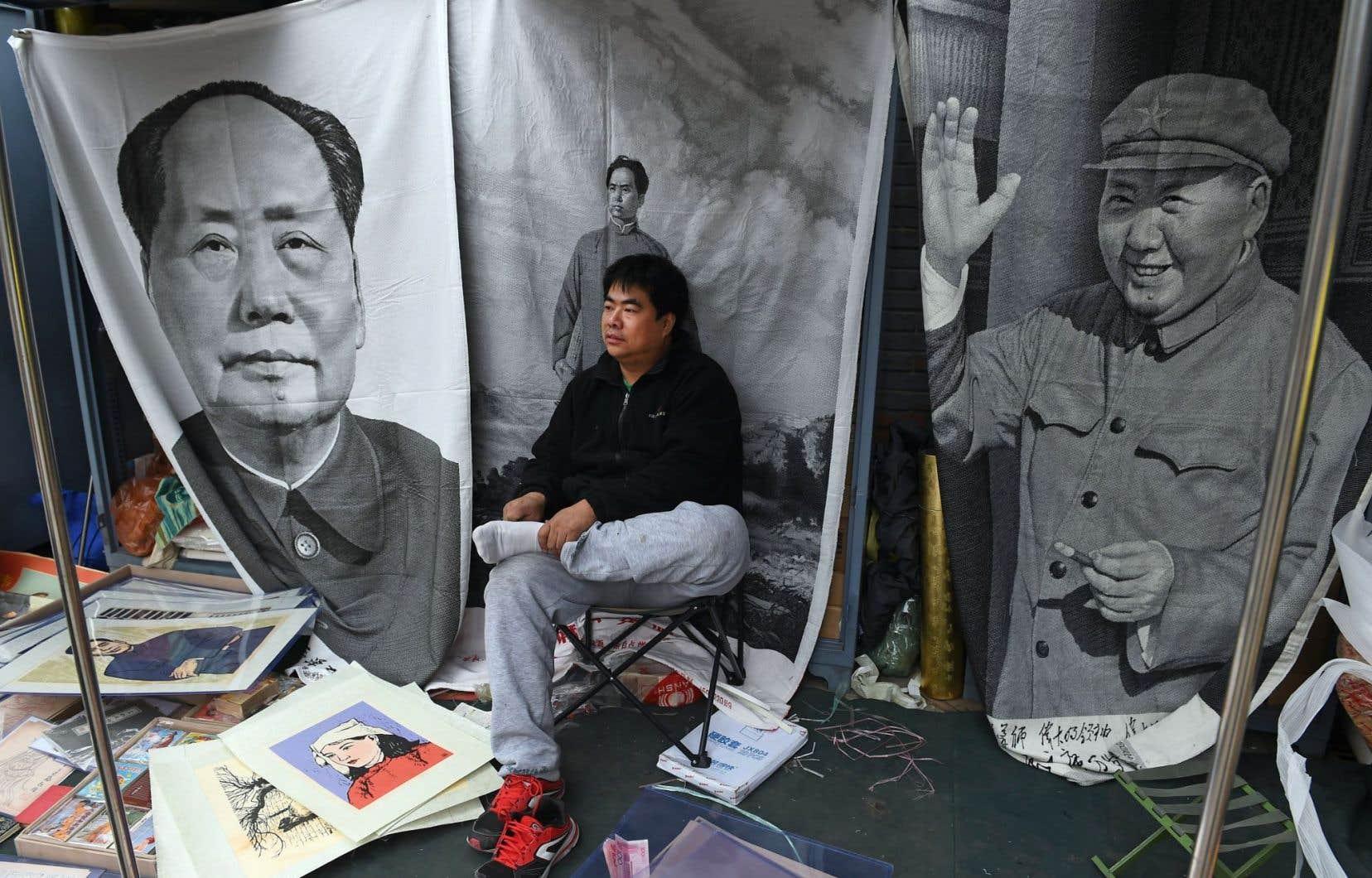 Dans une rue de Pékin, un homme vend des affiches représentant différents personnages, dont Mao Zedong. La Chine est en train de changer son modèle d'affaires, ce qui crée de l'incertitude en raison de l'influence qu'elle exerce sur l'économie mondiale.