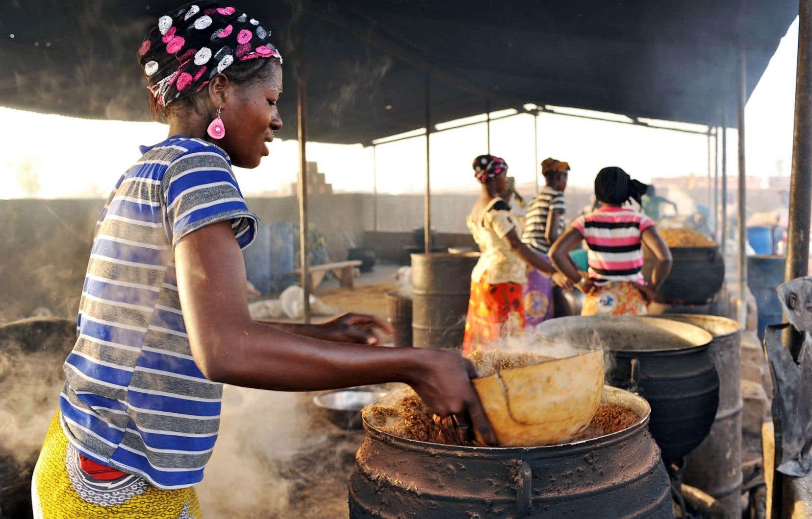 Asita Sana étuve du riz au centre d'étuvage de l'Union des groupements d'étuveuses de riz de Bama, au Burkina Faso.
