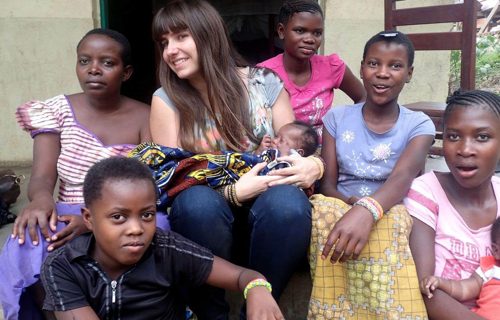 Magali Videau avec les résidentes de la maison Amani à Beni. L'enfant qu'elle tient dans ses bras s'appelle Noella et elle est née le 24décembre 2014. C'est le fruit du viol de sa jeune mère de 16ans (la jeune fille au chandail rose) durant sa captivité au sein du groupe de miliciens d'où elle s'est enfuie en juillet2014. Elle a été hébergée au centre de son septième mois de grossesse jusqu'à un mois après l'accouchement.