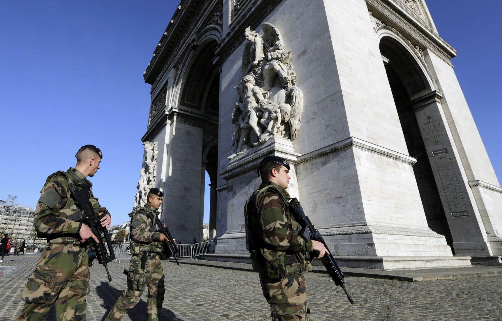 Des soldats gardaient l'Arc de triomphe, haut lieu touristique, dimanche à Paris. La ville pourrait connaître une saison tranquille.