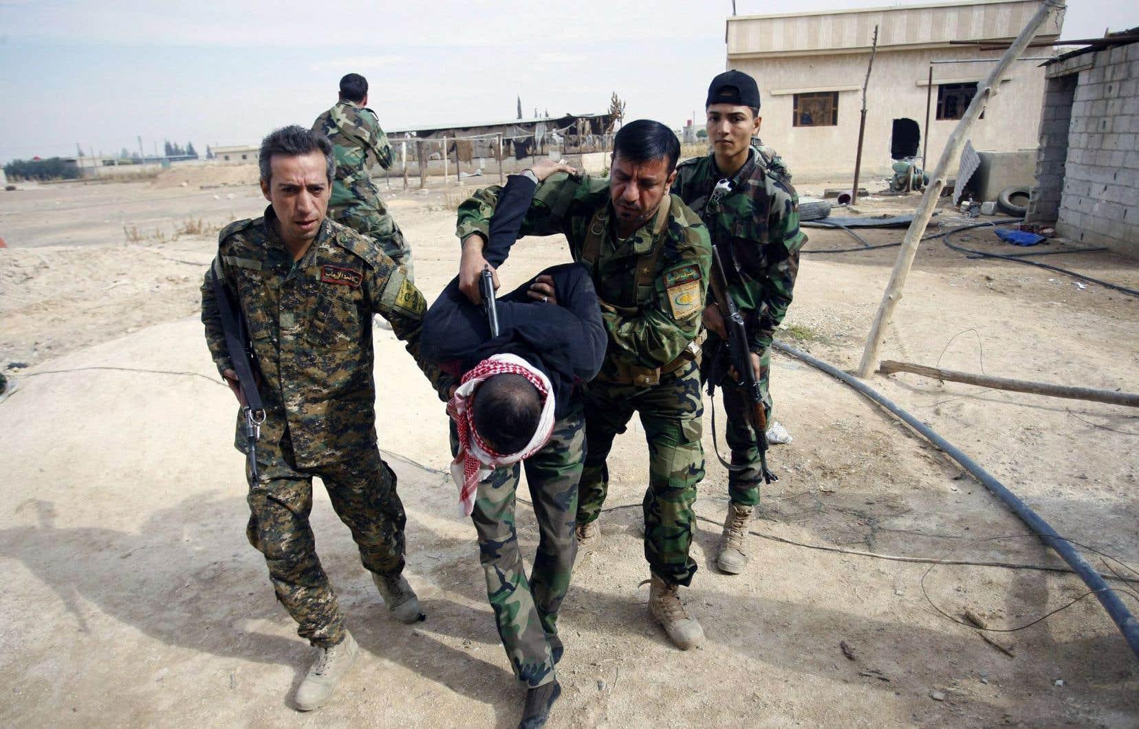 Syrie, novembre2013. Des militaires chiites conduisent en prison un membre sunnite de l'Armée syrienne libre.