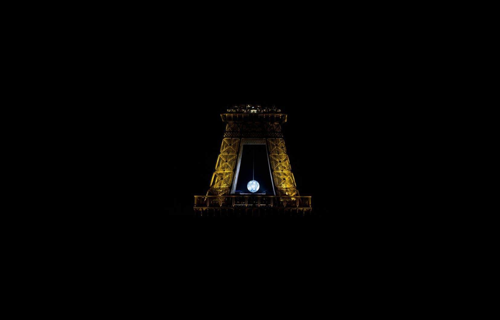 Le globe Earth Crisis, de l'artiste américain Shepard Fairey, a été suspendu à la tour Eiffel en préparation pour la conférence sur le climat.