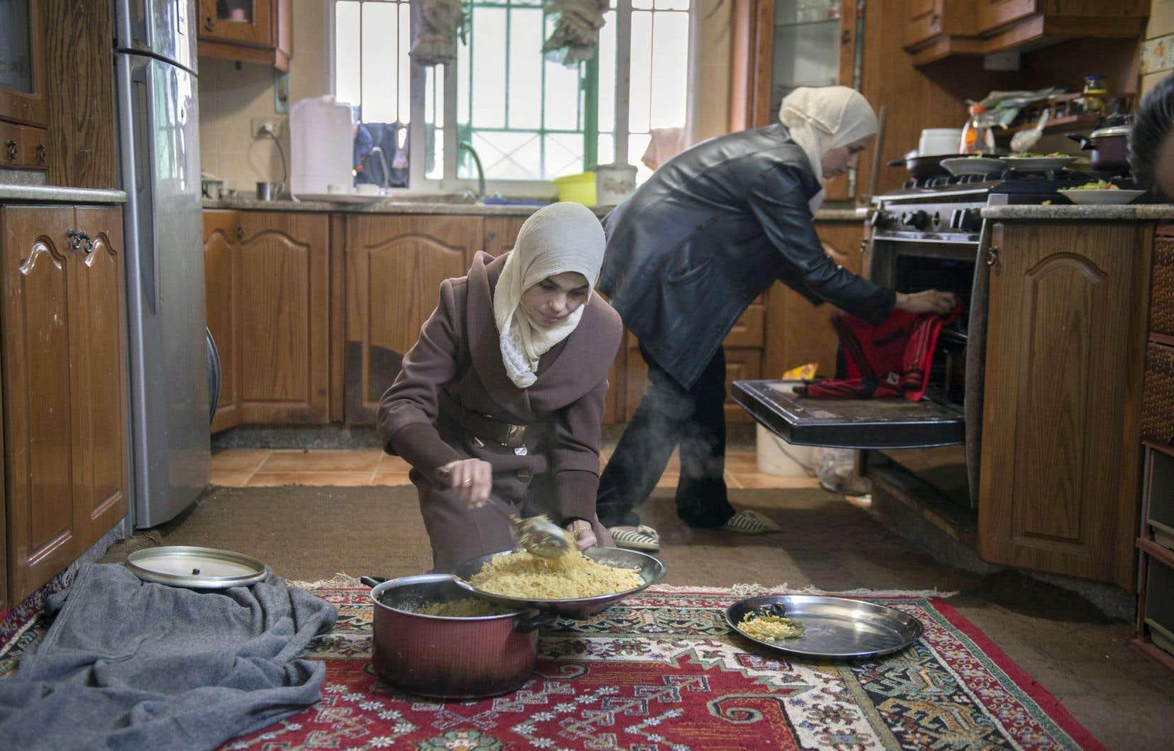 Deux réfugiées syriennes (qui ont fait une demande d'immigration au Canada) cuisinent dans un appartement en Jordanie.