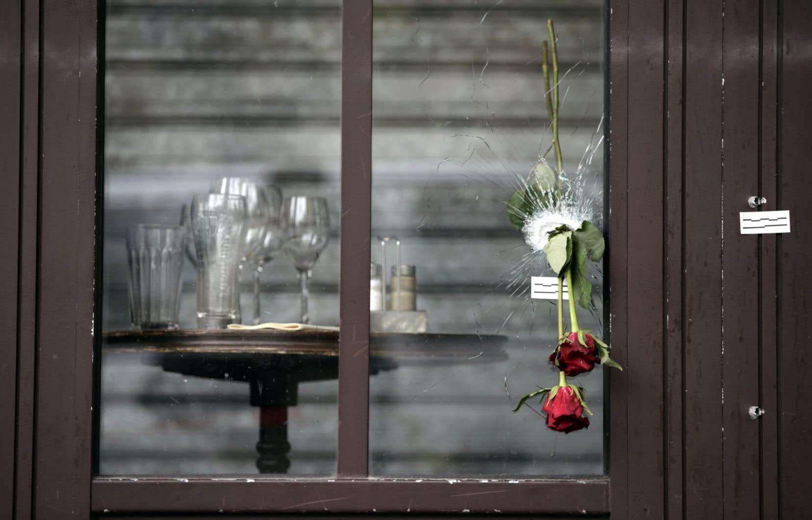 Des roses ont été placées dans le trou laissé par une balle d'une fenêtre du café À la bonne bière, à Paris.