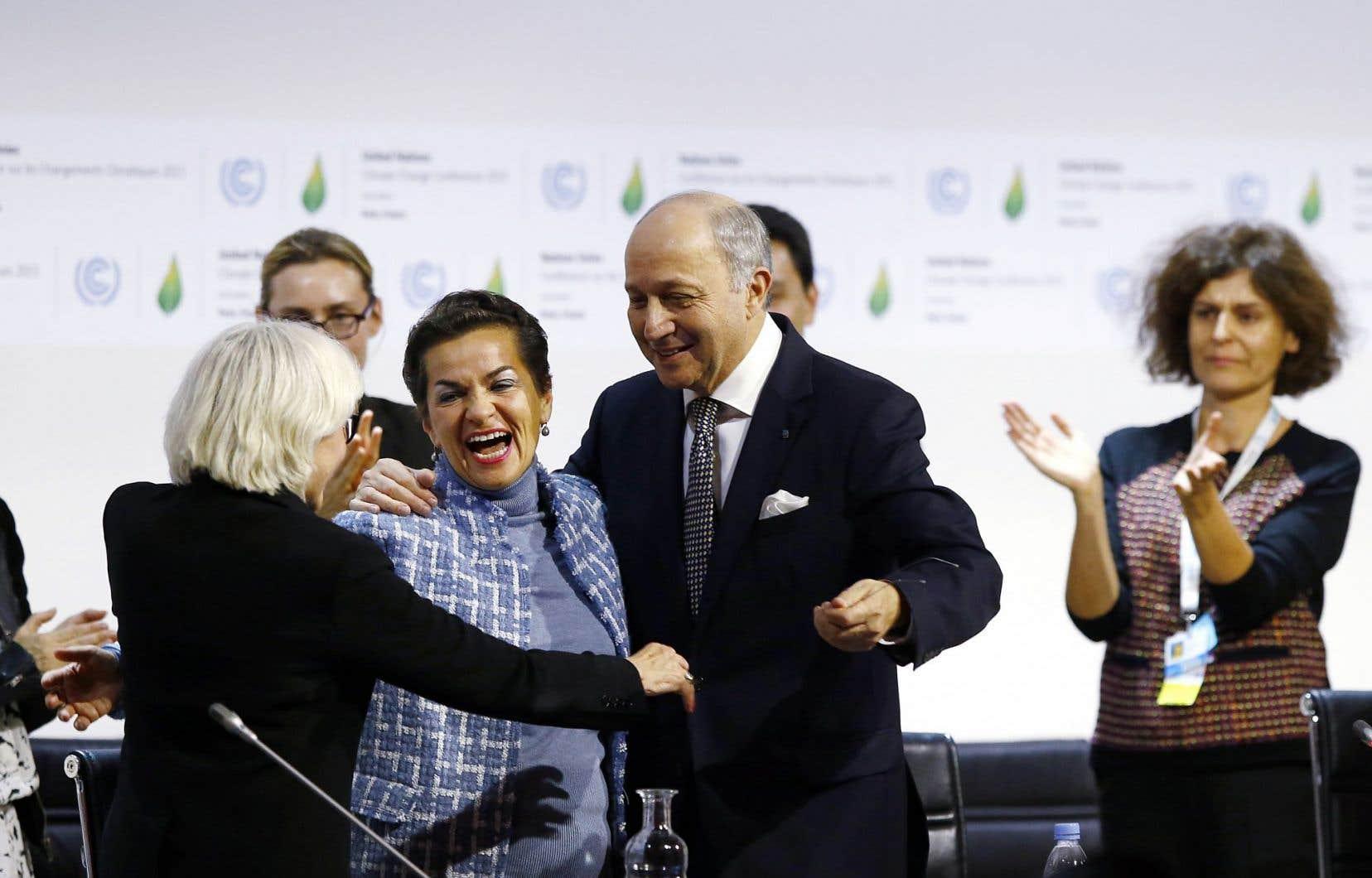 C'est dans l'euphorie que les dirigeants ont adopté l'Accord de Paris, samedi. Ci-dessus, Christiana Figueres, la chef des Nations unies pour la question climatique (au centre), faisant une accolade à la déléguée française Laurence Tubiana, et au président de la COP21, Laurent Fabius.