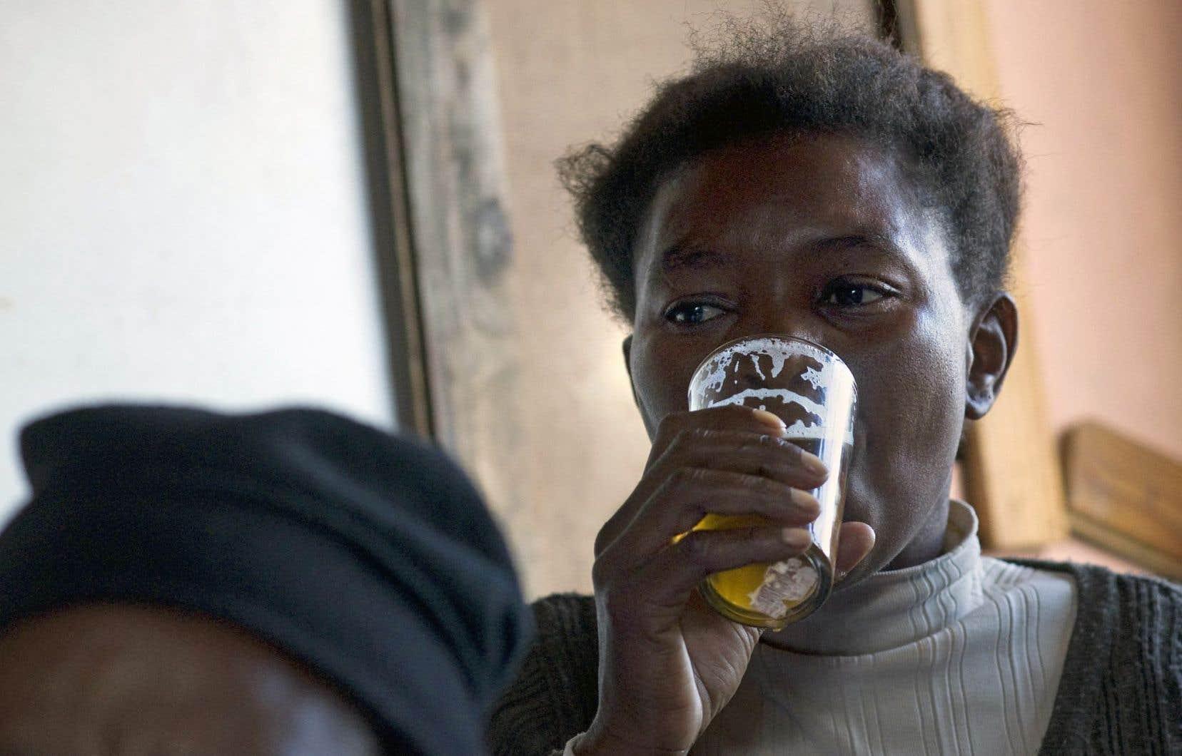 Une femme boit une bière dans une taverne illégale d'Afrique du Sud. La consommation de bières artisanales fait des centaines de morts chaque année sur le continent africain.