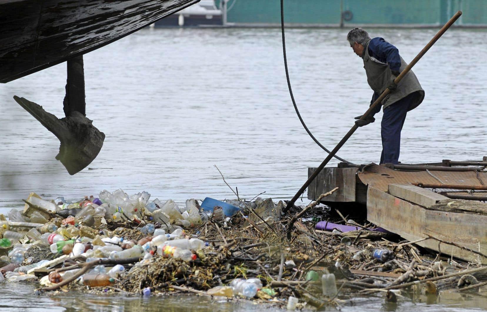 Un homme récupère des bouteilles de plastique au milieu d'autres déchets dans la rivière Sava, à Belgrade.