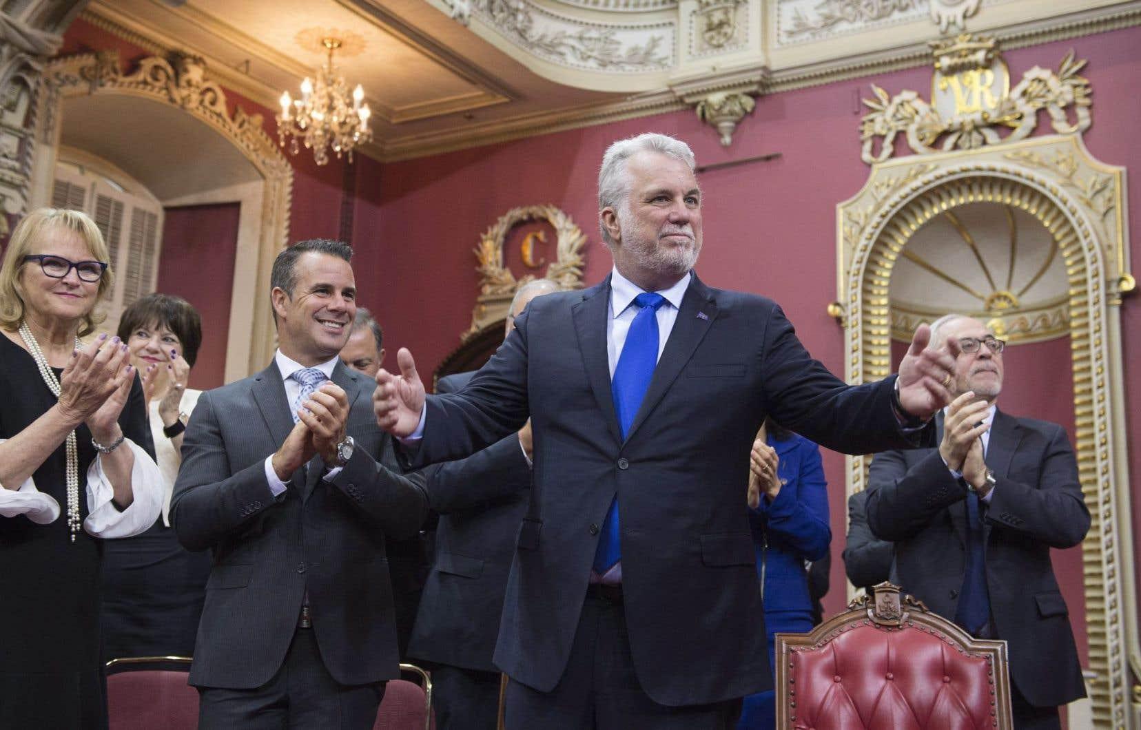 Philippe Couillard est applaudi par des membres de son cabinet, dont Nicole Ménard (présidente du caucus), Stéphane Billette (whip) et Carlos Leitão (Finances).