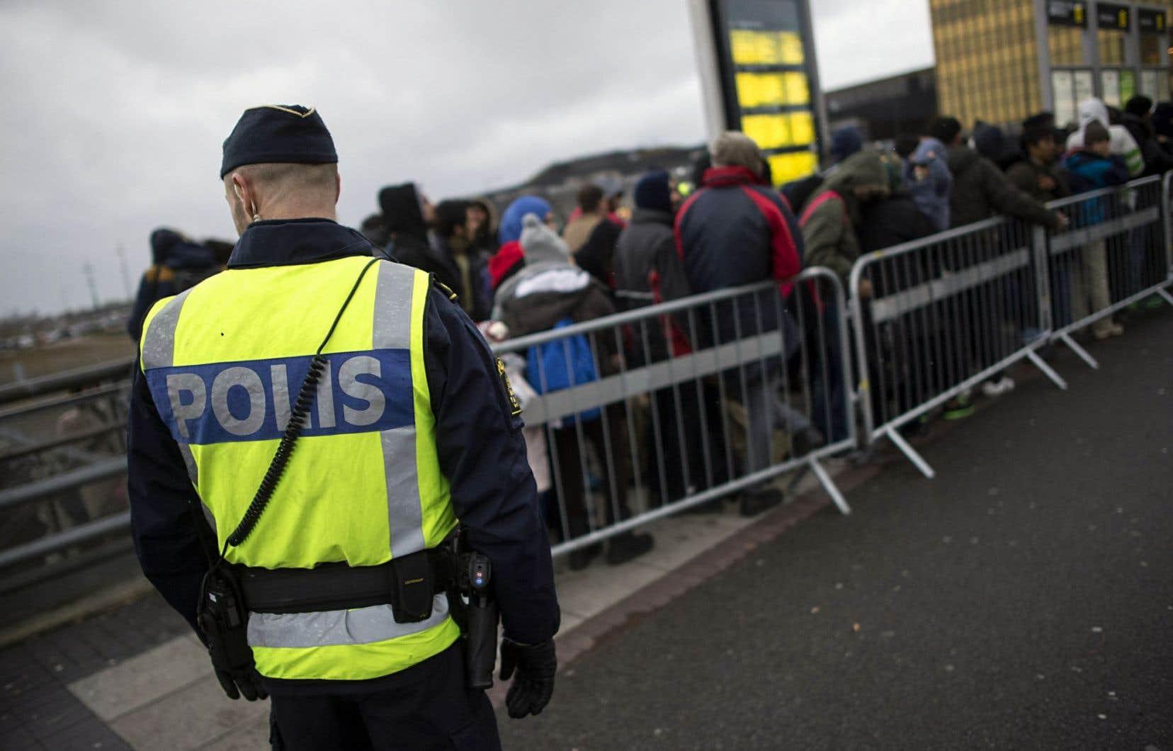 Un policier surveillant l'arrivée de nouveaux arrivants à Malmo en novembre 2015
