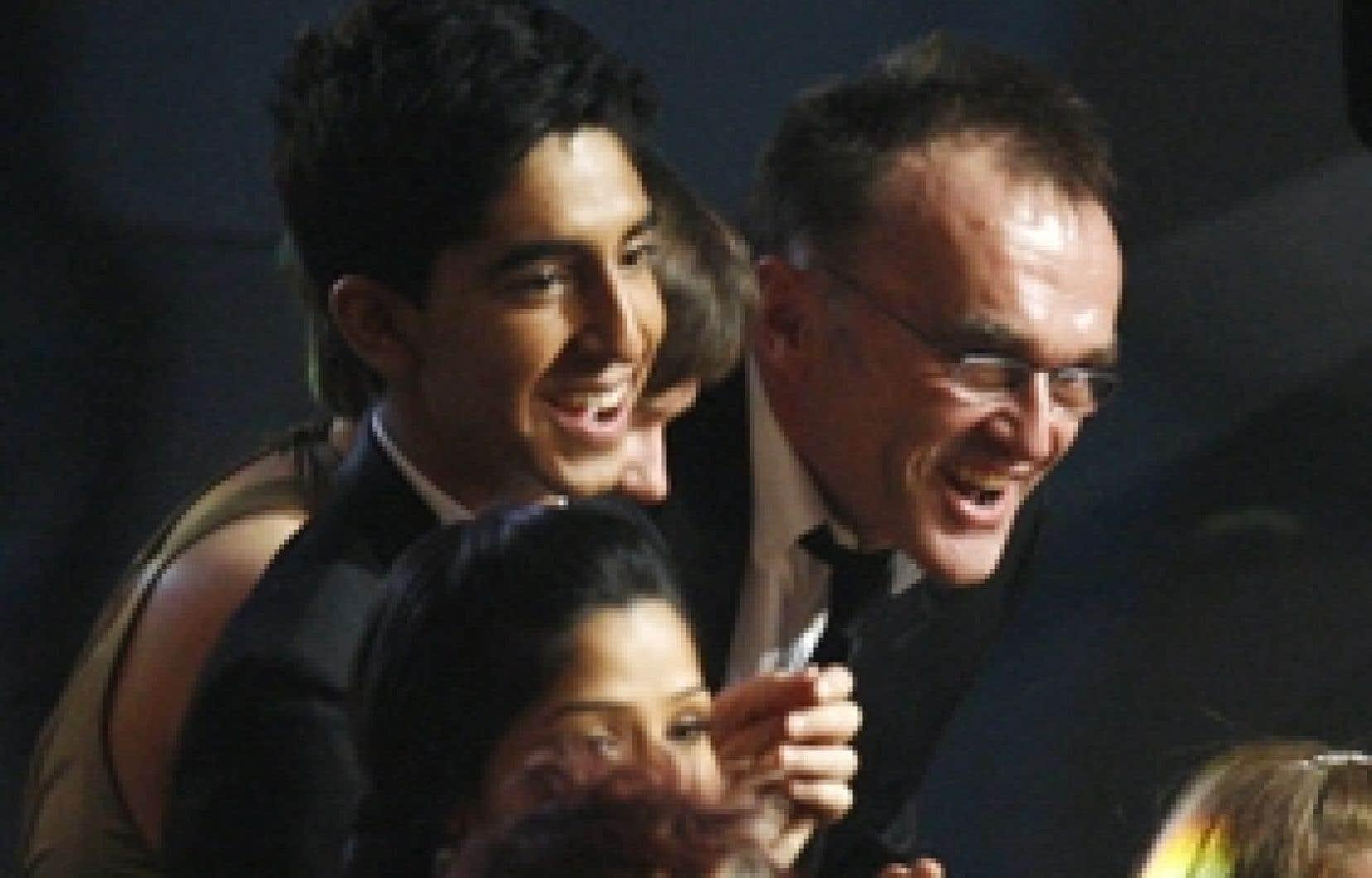 Dev Patel (à gauche), acteur principal de Slumdog Millionnaire, et le réalisateur du film, Danny Boyle, expriment leur joie au moment de remporter l'Oscar du meilleur montage, hier, à Los Angeles.