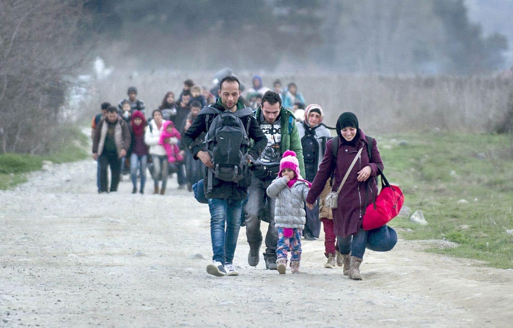 Des migrants originaires de la Syrie et de l'Irak ont franchi mardi la frontière de la Grèce et de la Macédoine.