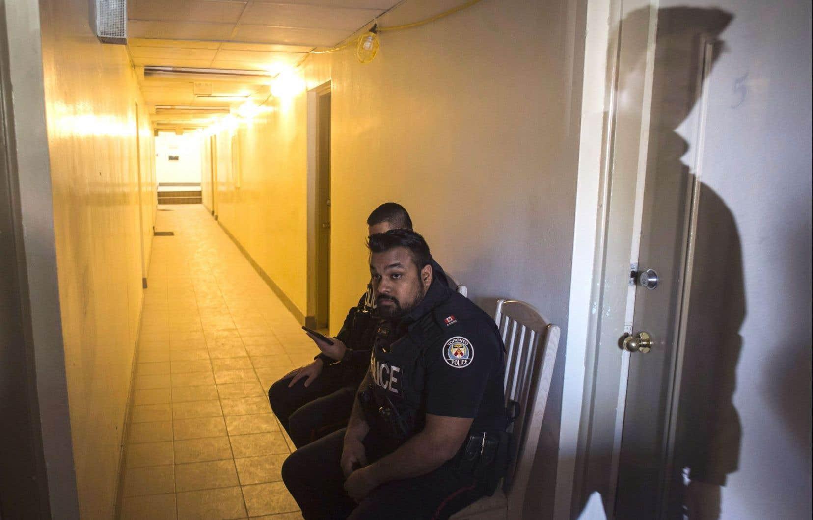 Des policiers gardent l'entrée de la résidence du suspect, Ayanle Hassan Ali, mardi à Etobicoke.
