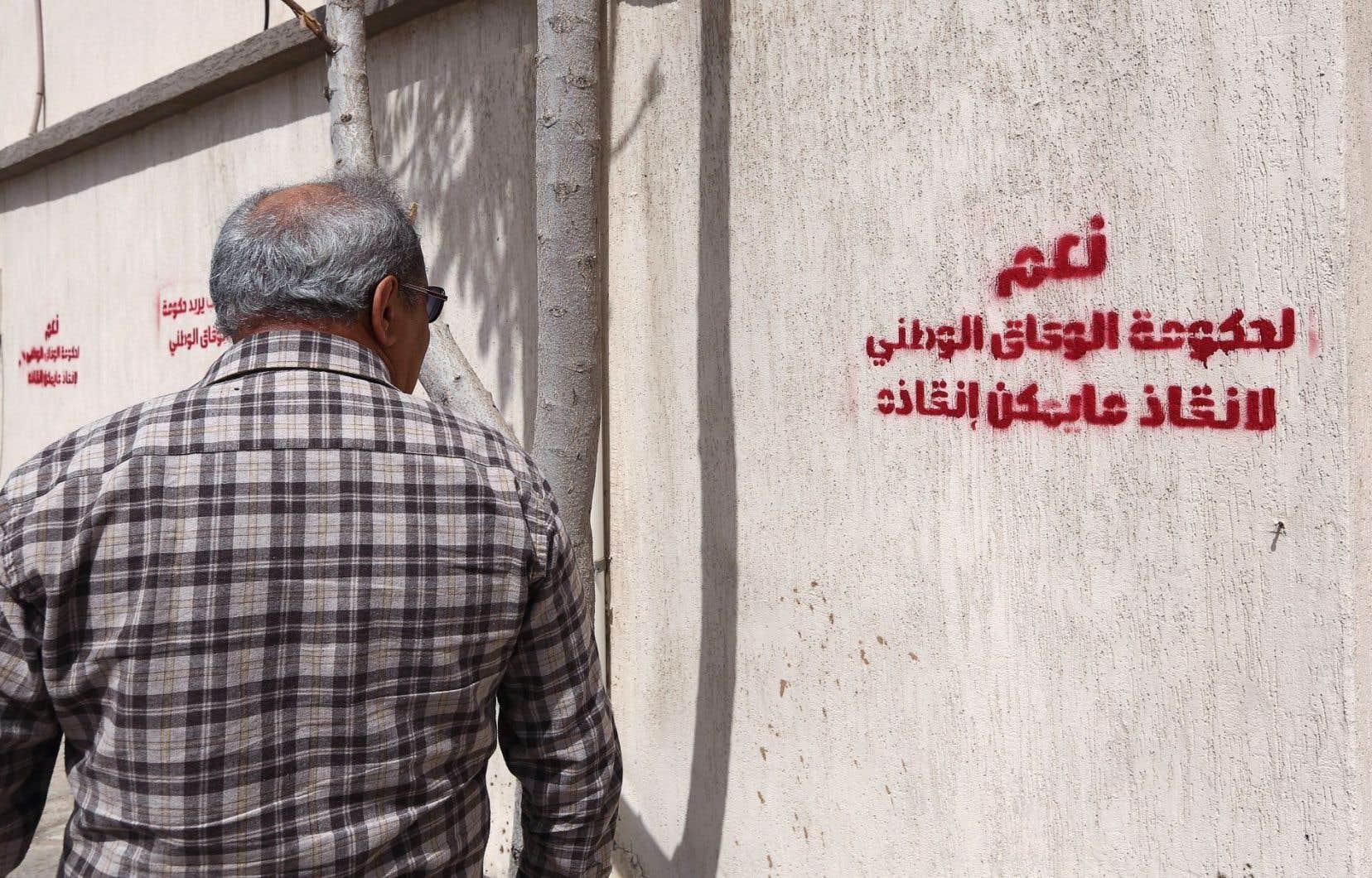 Un homme passe devant un graffiti écrit en arabe: «Oui au gouvernement d'union nationale pour sauver ce qui peut encore l'être.»