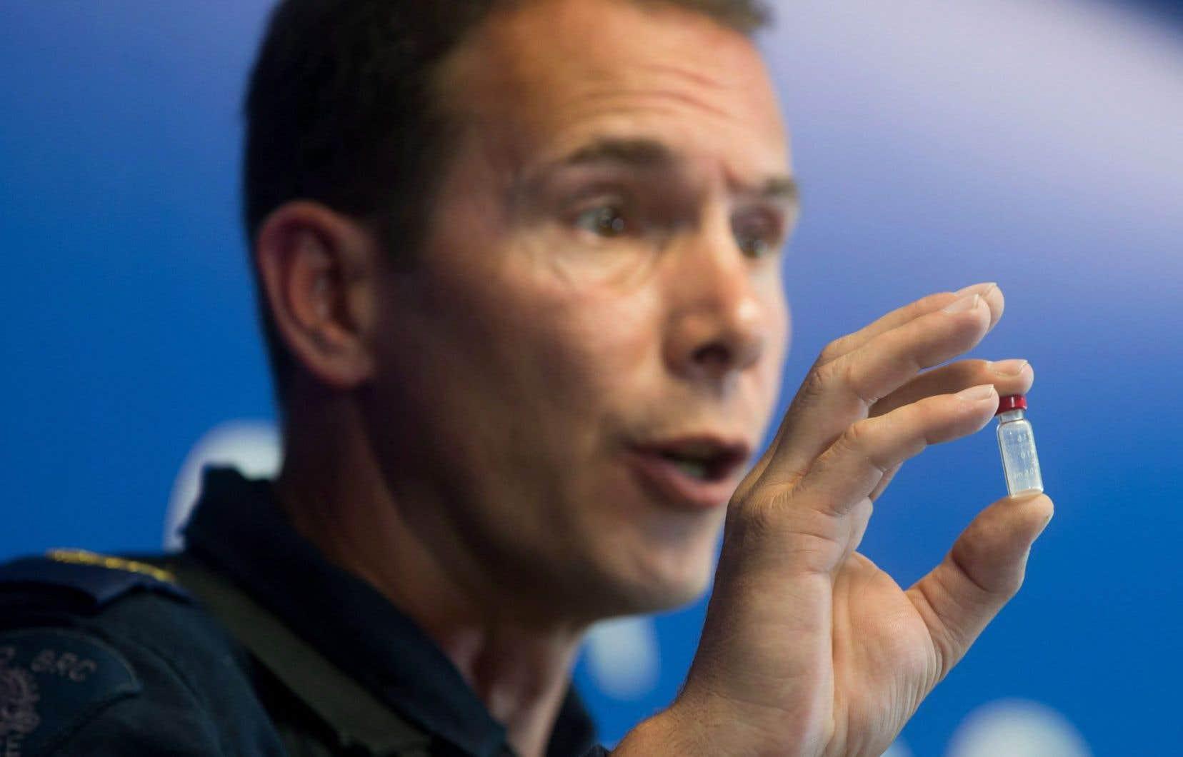 Lors d'une conférence de presse à Surrey, en Colombie-Britannique, un agent de la GRC montre une fiole contenant une dose de fentanyl, opioïde puissant, qui suffit pour tuer une personne.