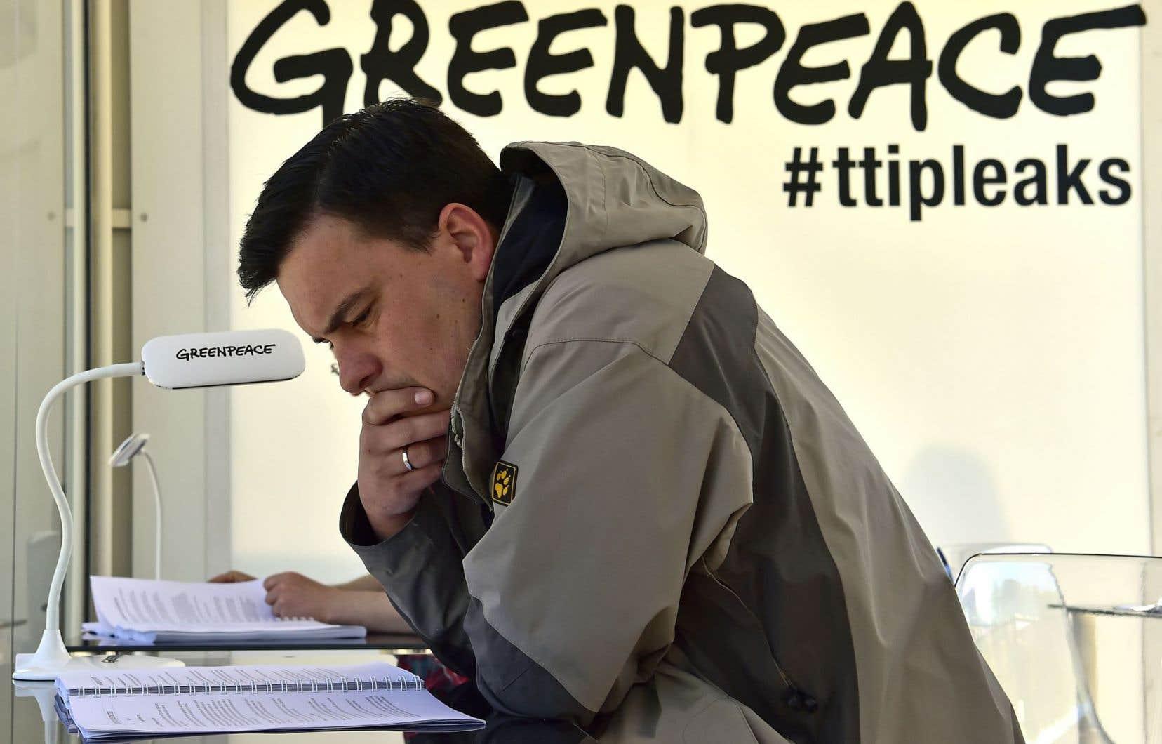 En face de la porte de Brandebourg, à Berlin, un homme lit un document secret sur l'accord de libre-échange entre l'Europe et les États-Unis que Greenpeace a rendu public lundi.