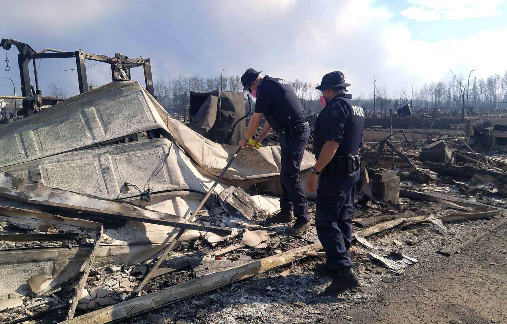 Des policiers de la GRC examinent les ruines de maisons détruites par l'incendie qui sévit à Fort McMurray.