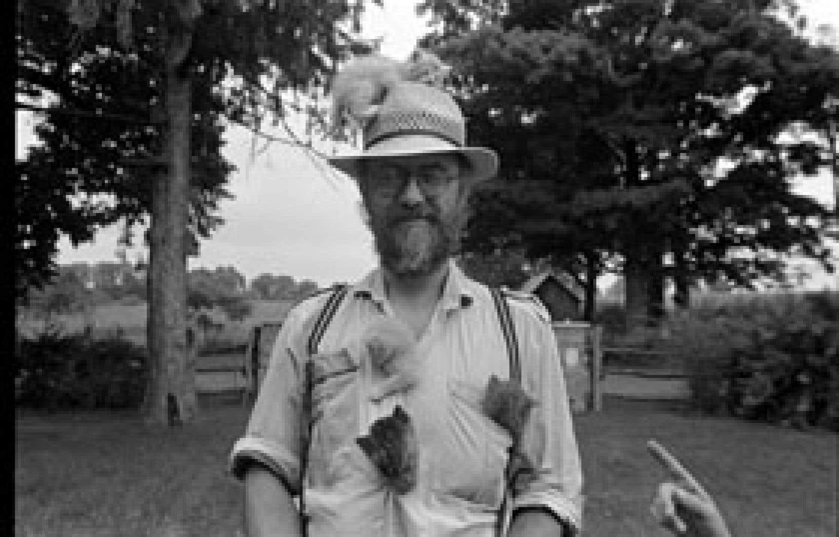 Le photographe Larry Towell dans sa ferme, des chatons installés sur lui. L'un d'eux grimpe sur son chapeau. La main d'un de ses enfants le montre du doigt. Photo: Larry Towell gracieuseté de Magnum Photo