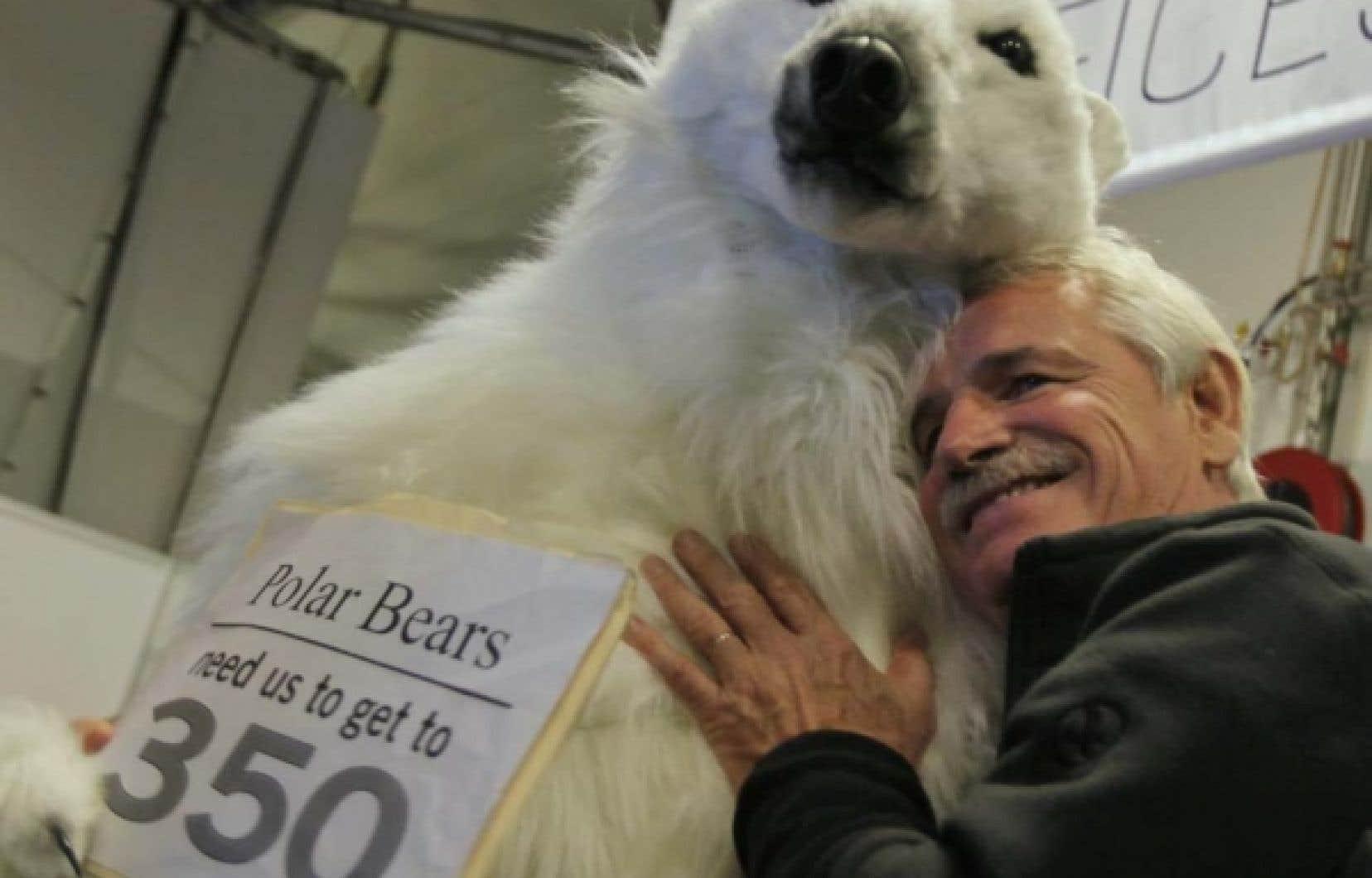 Le célèbre photographe Yann Arthus-Bertrand devant l'immeuble de la conférence de Copenhague, aujourd'hui, avec un militant déguisé en ours polaire.
