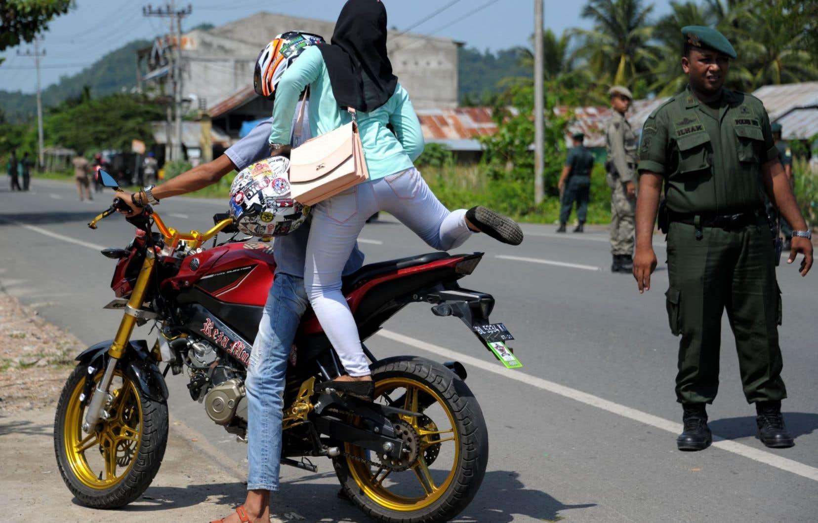 À Aceh Besar, dans la province d'Aceh, un policier interpelle deux motocyclistes à propos de leurs pantalons. Cette province du nord de Sumatra a interdit aux musulmanes de porter des vêtements ajustés. Aceh est la seule province indonésienne à appliquer la charia.