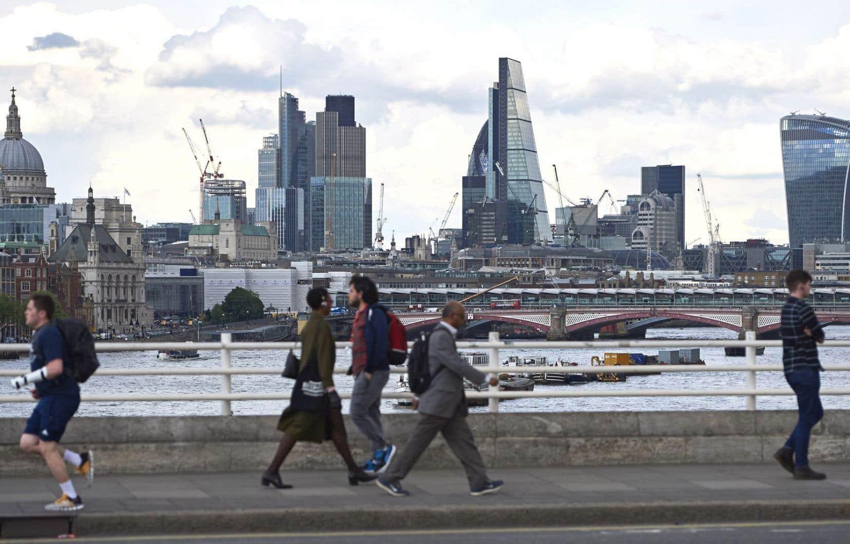 À Londres, des piétons marchent sur le pont Waterloo, face à la City.