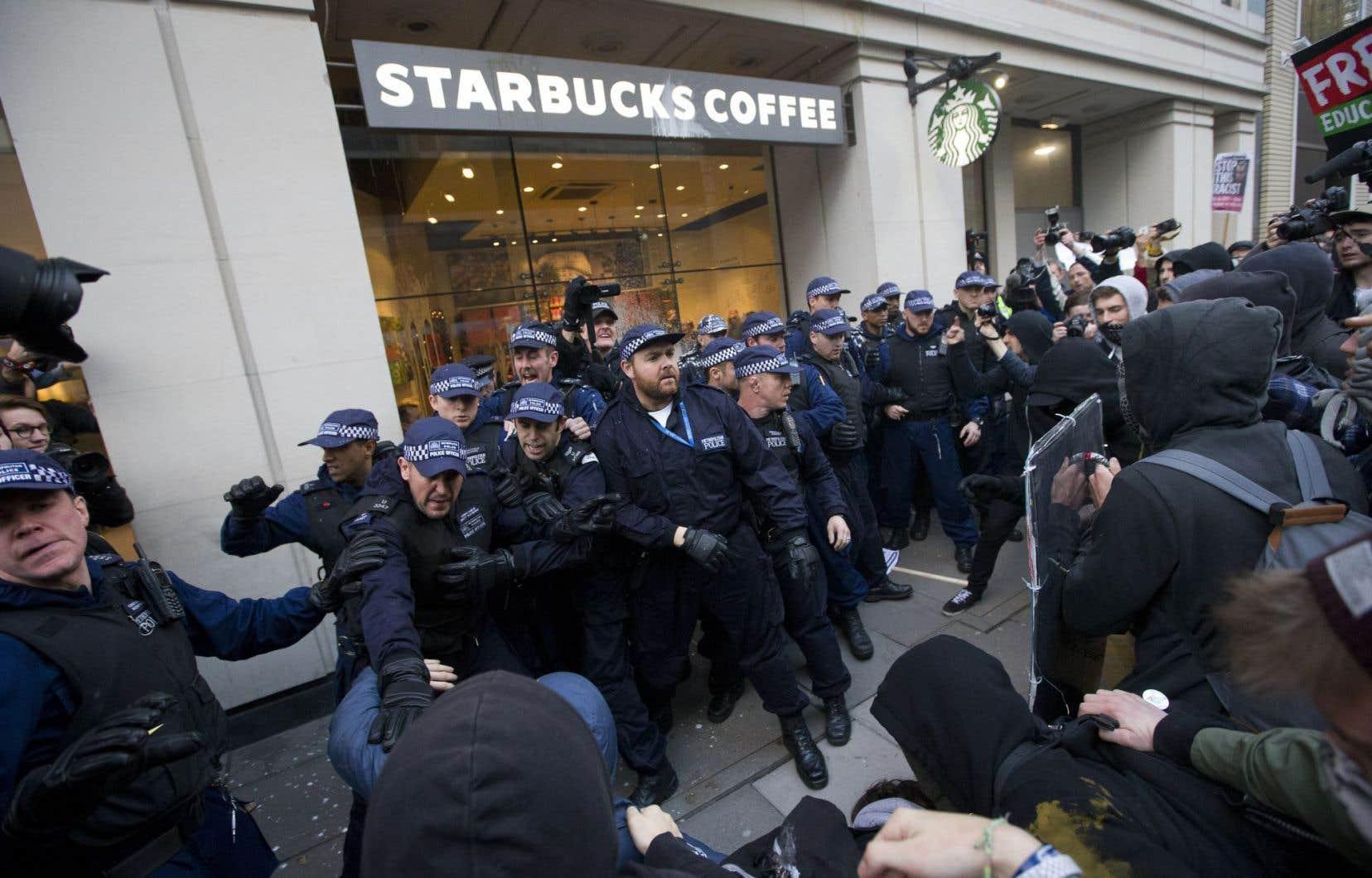 Des membres du service de police de Londres protégeaient l'entrée d'un café Starbucks lors d'une manifestation contre l'austérité, dans la capitale britannique, en novembre 2014. La mégachaîne américaine a souvent été la cible de mouvements de protestation à cause de ses pratiques d'évitement fiscal dans divers pays.