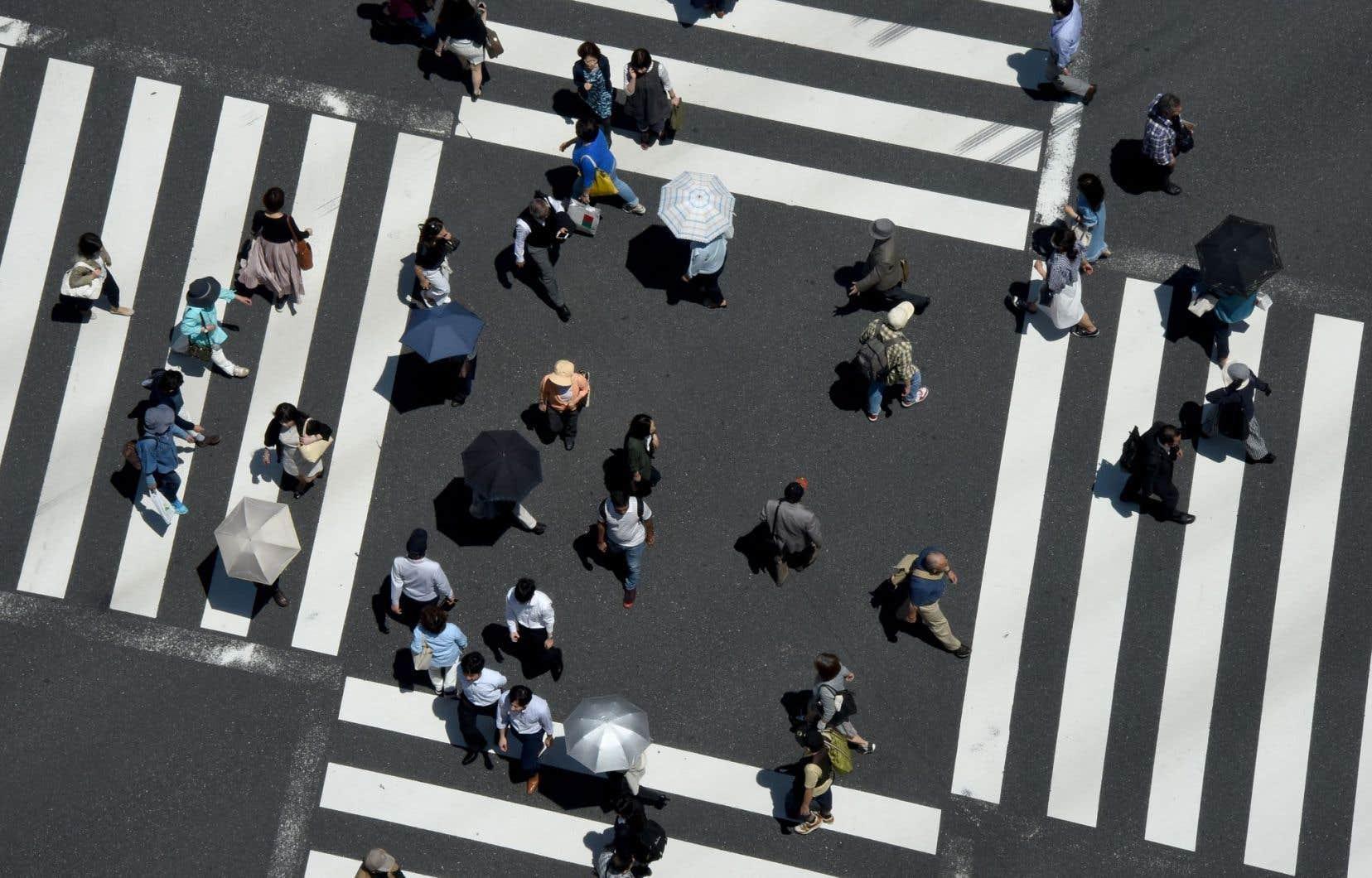 Des piétons traversent la rue à une intersection, à Tokyo. La croissance du Japon sera de seulement 0,7 % cette année, et de 0,4 % en 2017.
