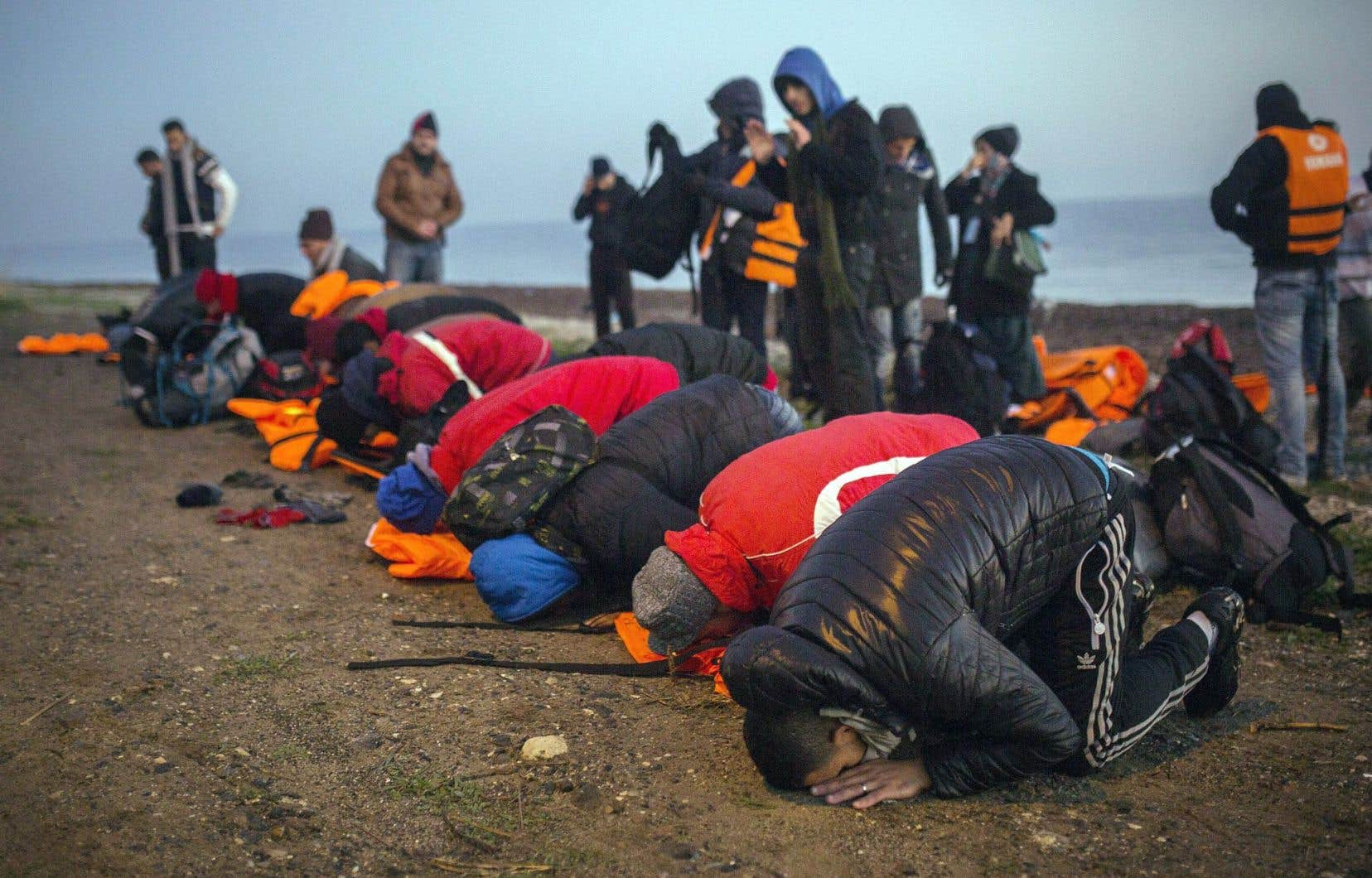 Des intervenants rappellent la vulnérabilité des réfugiés, qui pourraient se sentir forcés d'obéir. Ci-dessus, des migrants musulmans font leur prière après avoir réussi à atteindre une plage grecque.