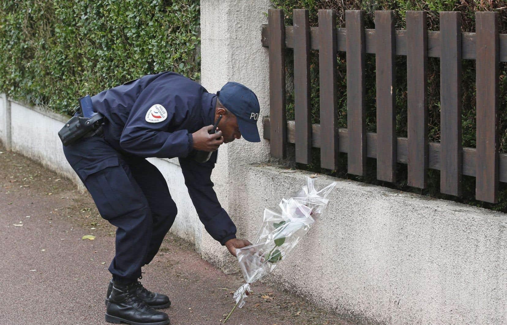 Un policier dépose une de fleur devant le domicile des victimes.