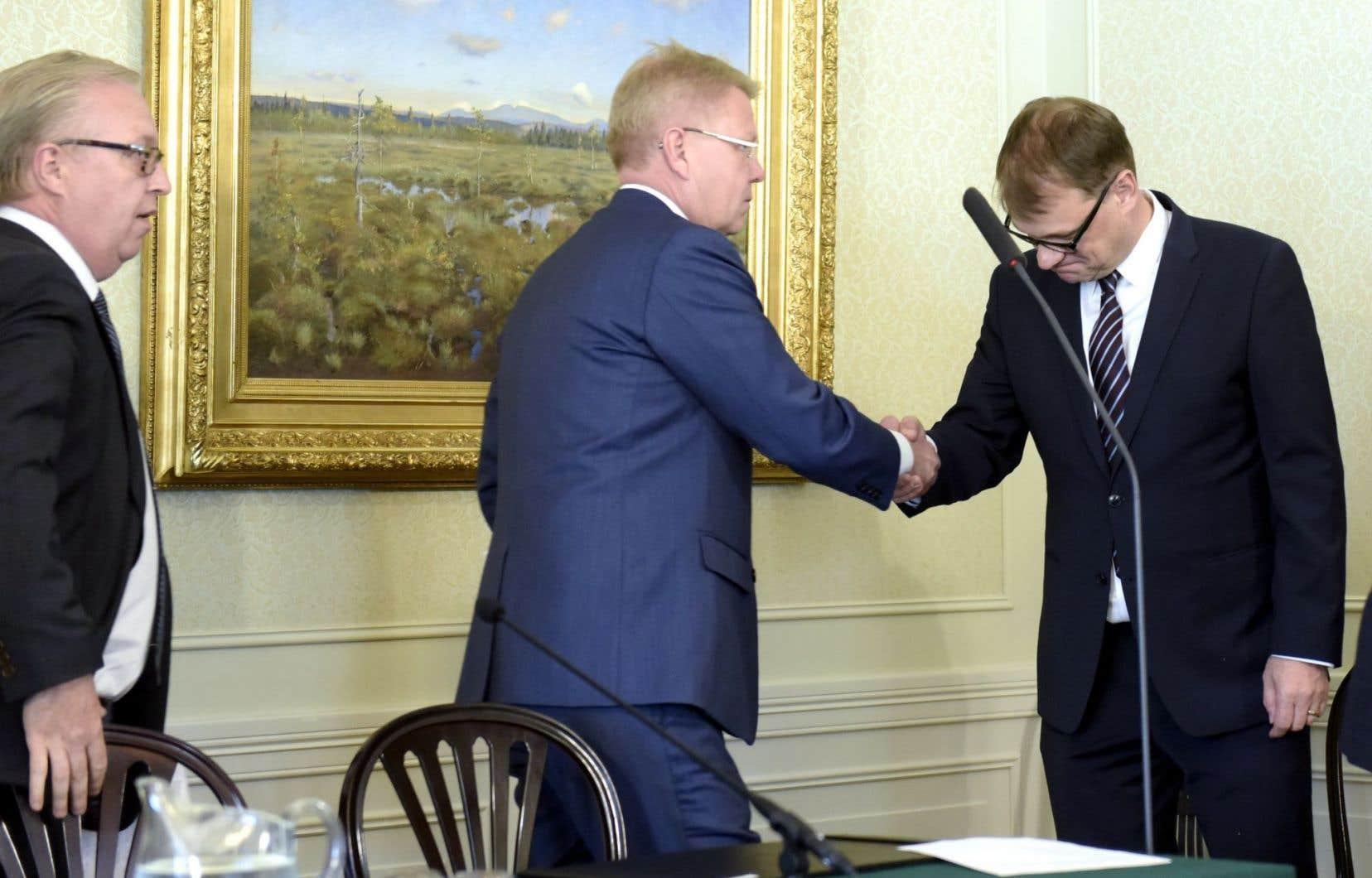 Le premier ministre finlandais, Juha Sipila (à droite), et le directeur général de la plus importante organisation d'affaires de la Finlande, Jyri Hakamies, se sont serré la main à l'issue de la signature du «Pacte de compétitivité», mardi.