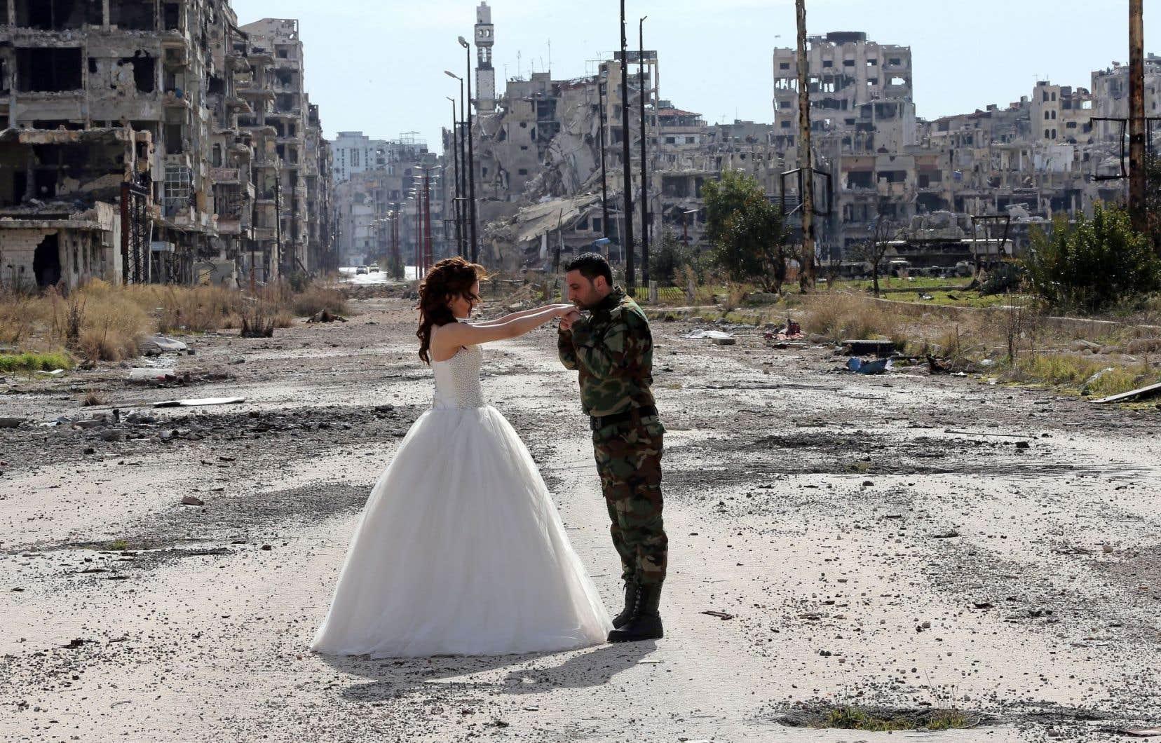 Des nouveaux mariés posent pour un photographe devant les ruines de Homs. Alors qu'elle était habitée par 650 000 personnes il y a quelques années, la ville ne compte plus que 200 000 habitants aujourd'hui.