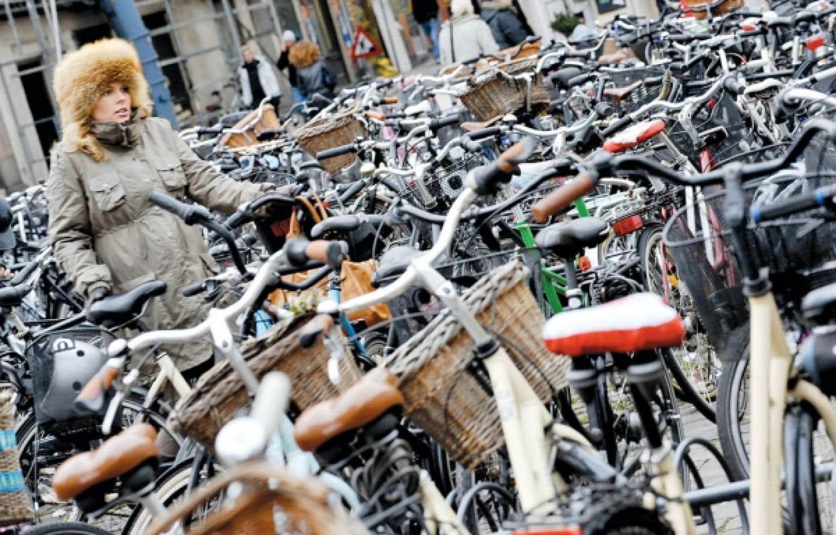 Une femme enceinte cherche un endroit où garer son vélo, au centre-ville de Copenhague.