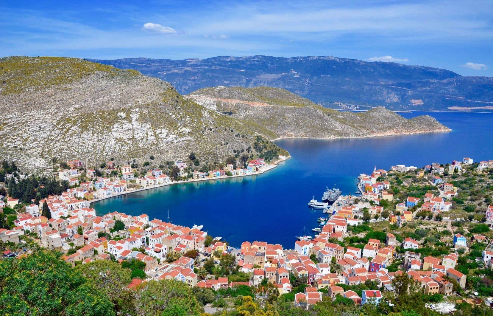 Du sommet de la falaise, vue sur le port en amphithéâtre, les maisons aux toits de tuiles rouges, la mer Méditerranée et la cité de Kas, en face, avec ses maisons blanches posées sur les Taurus qui se jettent dans la mer.