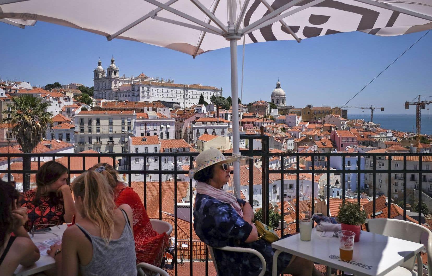 Des touristes profitent de la douceur de la vie lisboète sur l'esplanade à Portas do Sol, dans le centre de la capitale portugaise.