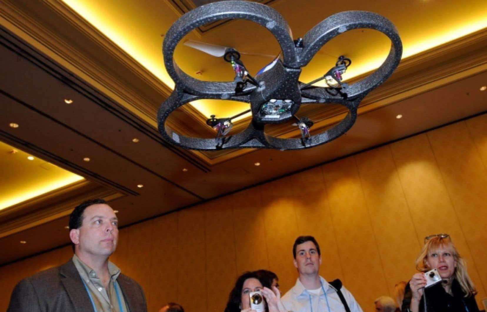 Des journalistes observent le vol d'un de l'AR drone, un robot piloté grâce à l'iPhone ou au baladeur iPod touch.