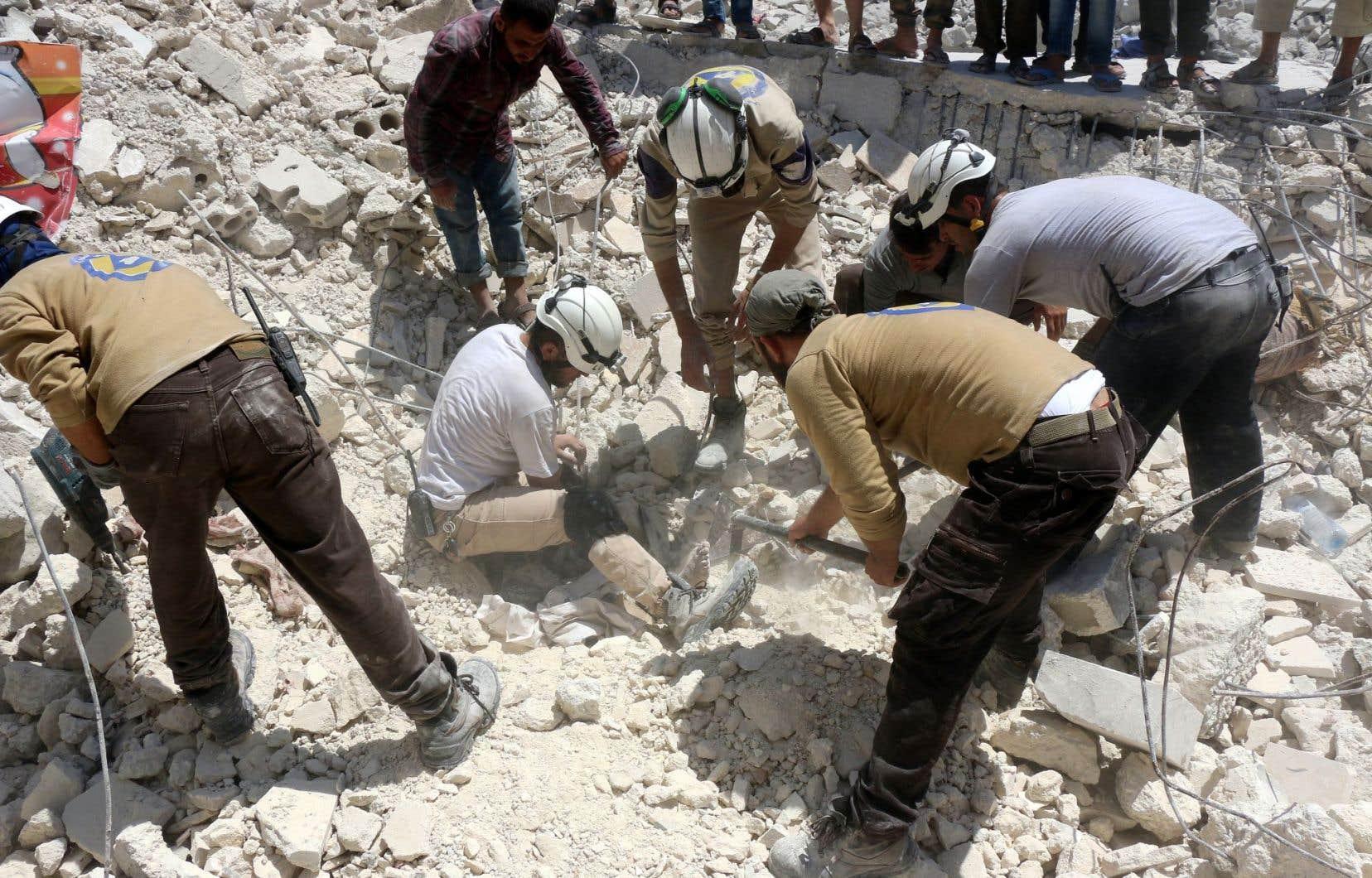Des civils recherchent des survivants dans les décombres d'un immeuble dans le nord de la ville d'Alep, à la suite de frappes aériennes du régime.