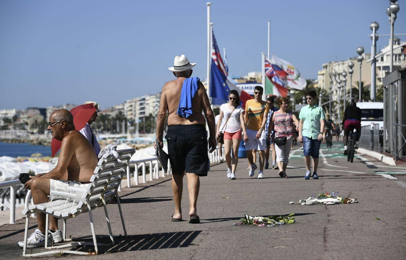 Sur la promenade des Anglais, des marcheurs circulent près des fleurs déposées au sol pour honorer la mémoire des victimes de l'attentat.
