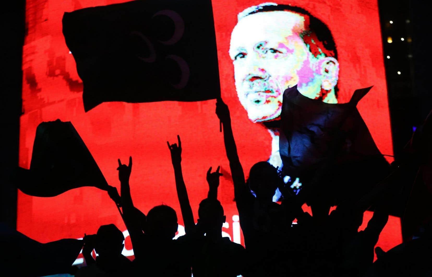 Le visage du président Erdogan apparaît sur un écran lors d'une manifestation en faveur du gouvernement à Ankara. Le régime a appelé les habitants à montrer leur soutien après la tentative de coup d'État.