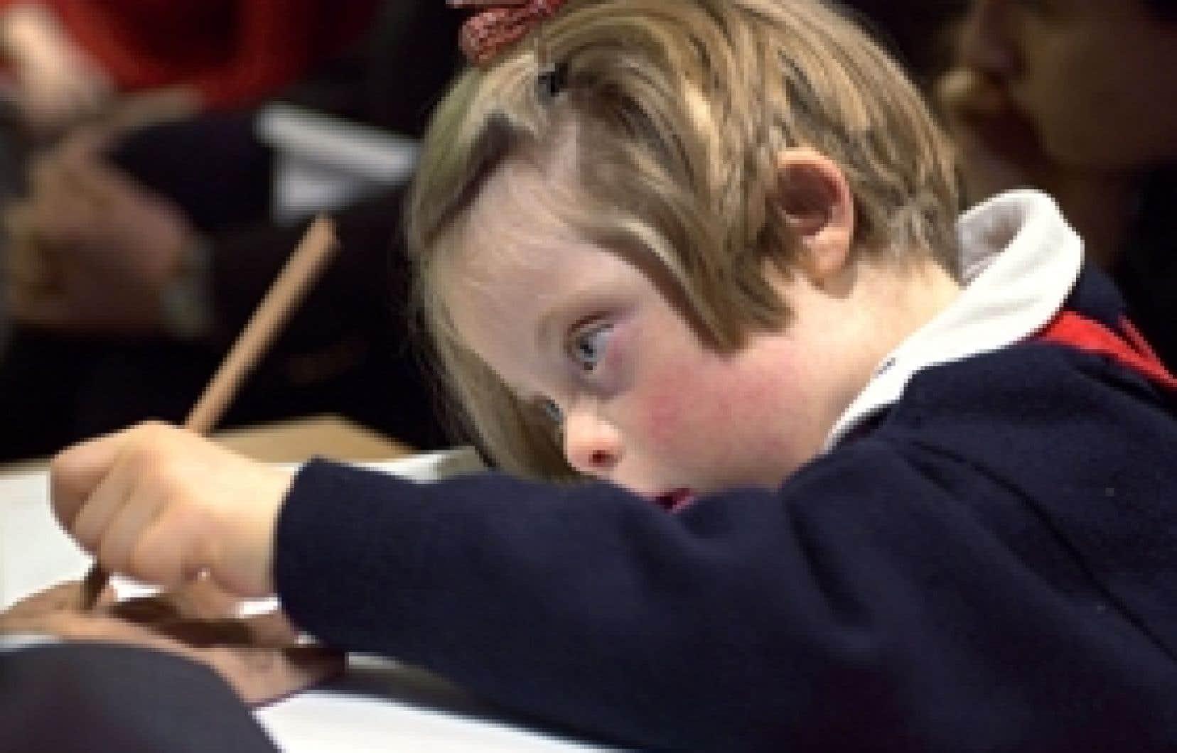 Anne, une enfant trisomique, dessine. Un test de dépistage pourrait être offert gratuitement à toutes les futures mères, le ministre québécois de la Santé s'étant montré favorable aux recommandations qui lui ont été faites en ce sens.