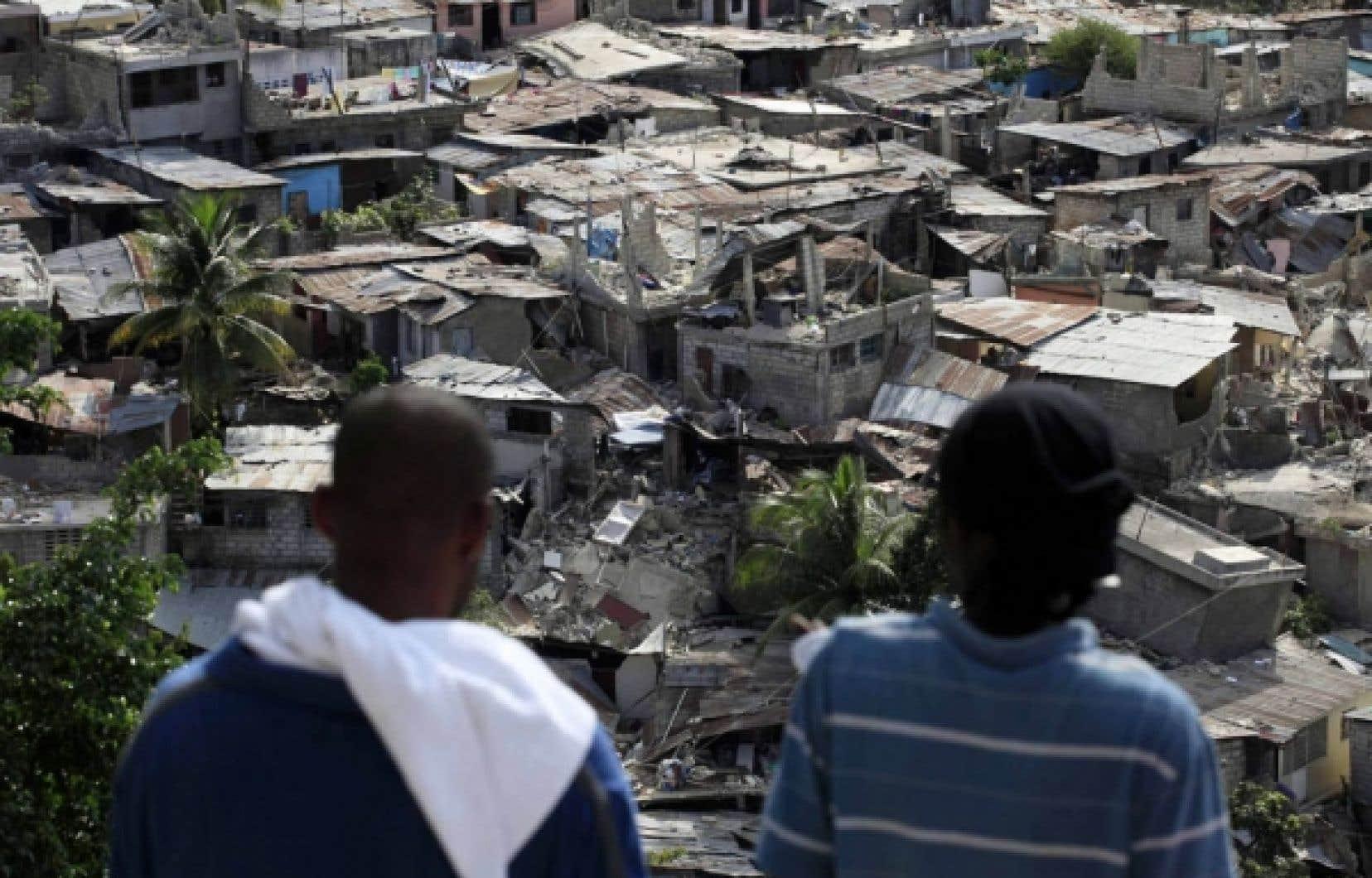 Deux hommes observent le désastre, du haut d'une des nombreuses collines qui entourent Port-au-Prince.