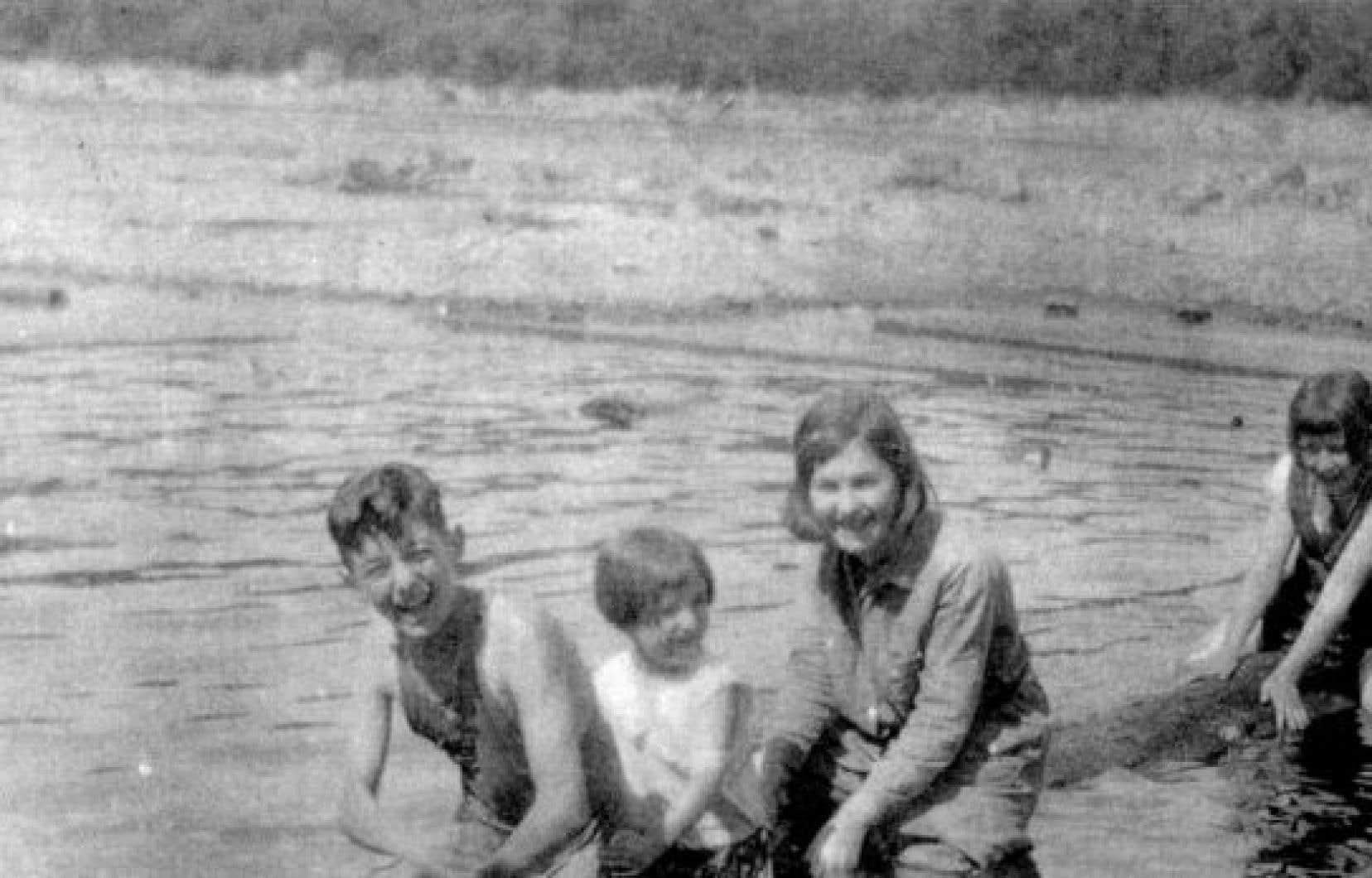 Sur cette photo de 1927, un jeune Félix Leclerc (à gauche) apparaît souriant, entouré de ses sœurs. Derrière, la pitoune flotte sur le Saint-Maurice.