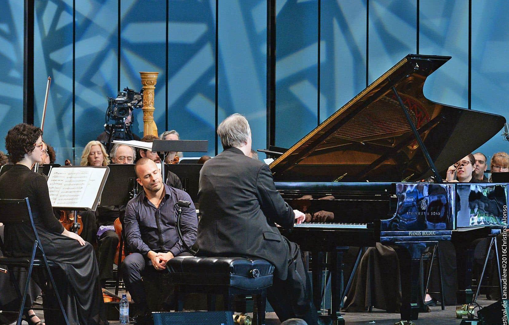 Le chef Yannick Nézet-Séguin, assis sur son podium, écoute les yeux fermés la lévitation musicale du pianiste américain Nicholas Angelich dans son rappel: le Prélude opus 32 n° 5 de Rachmaninov.